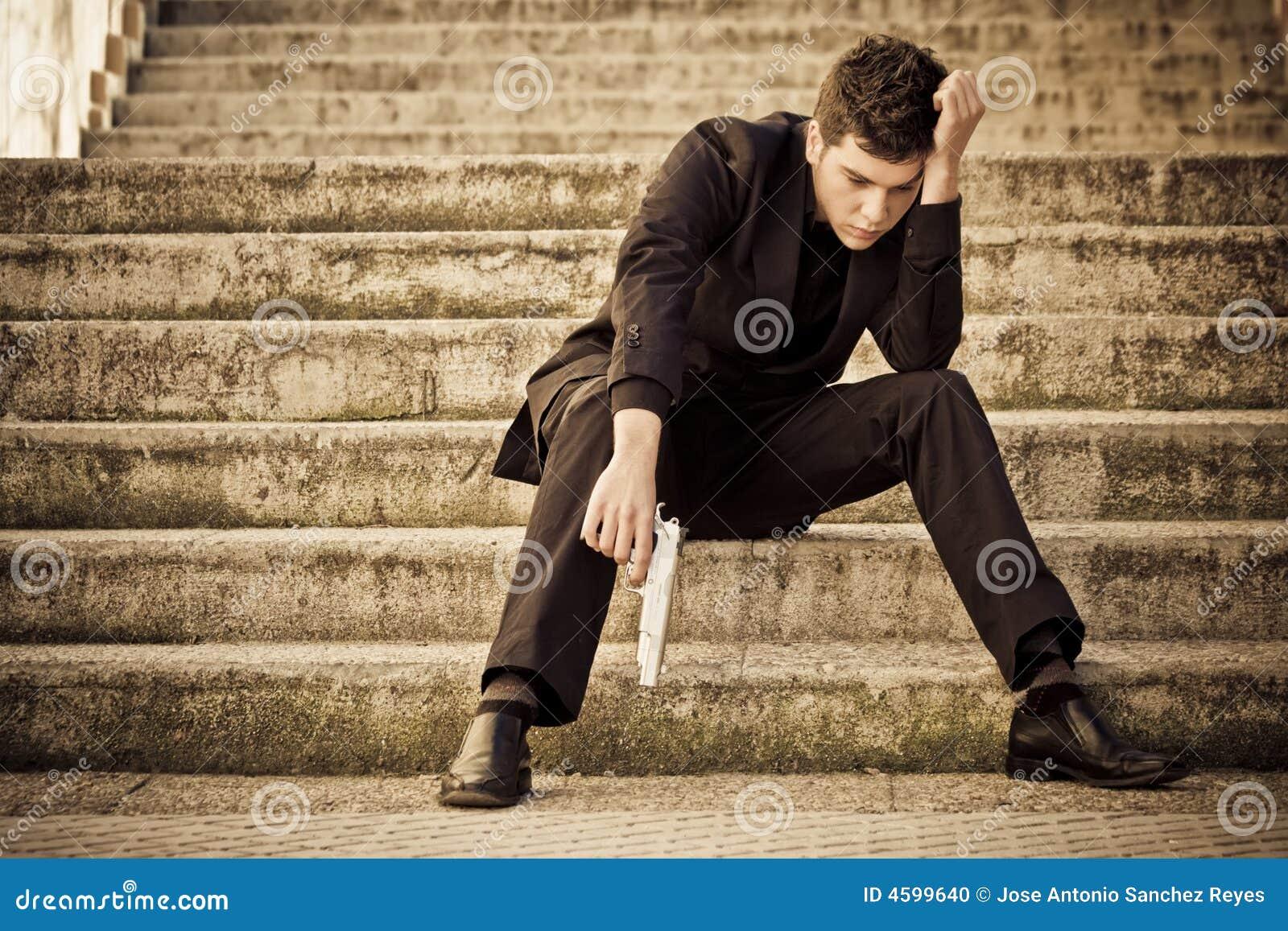 Homem armado dos jovens em escadas