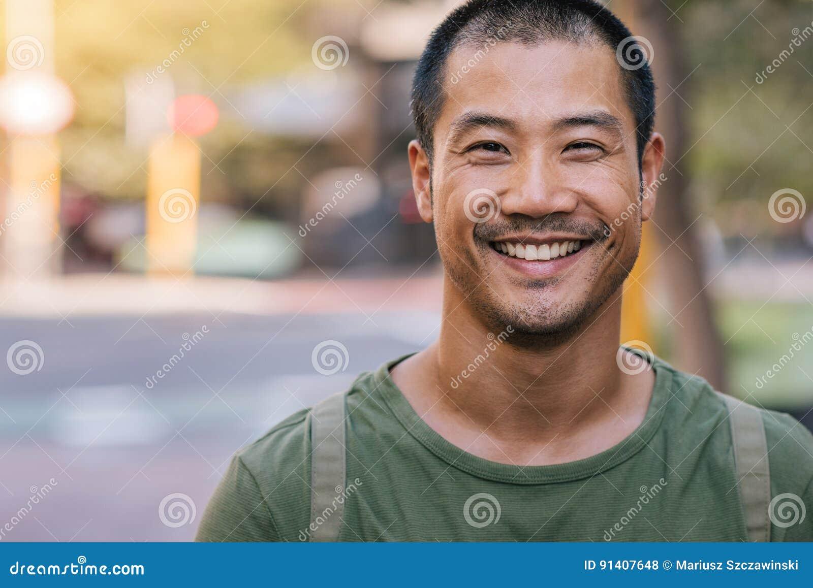 Homem asiático considerável que está em uma rua e em um sorriso da cidade