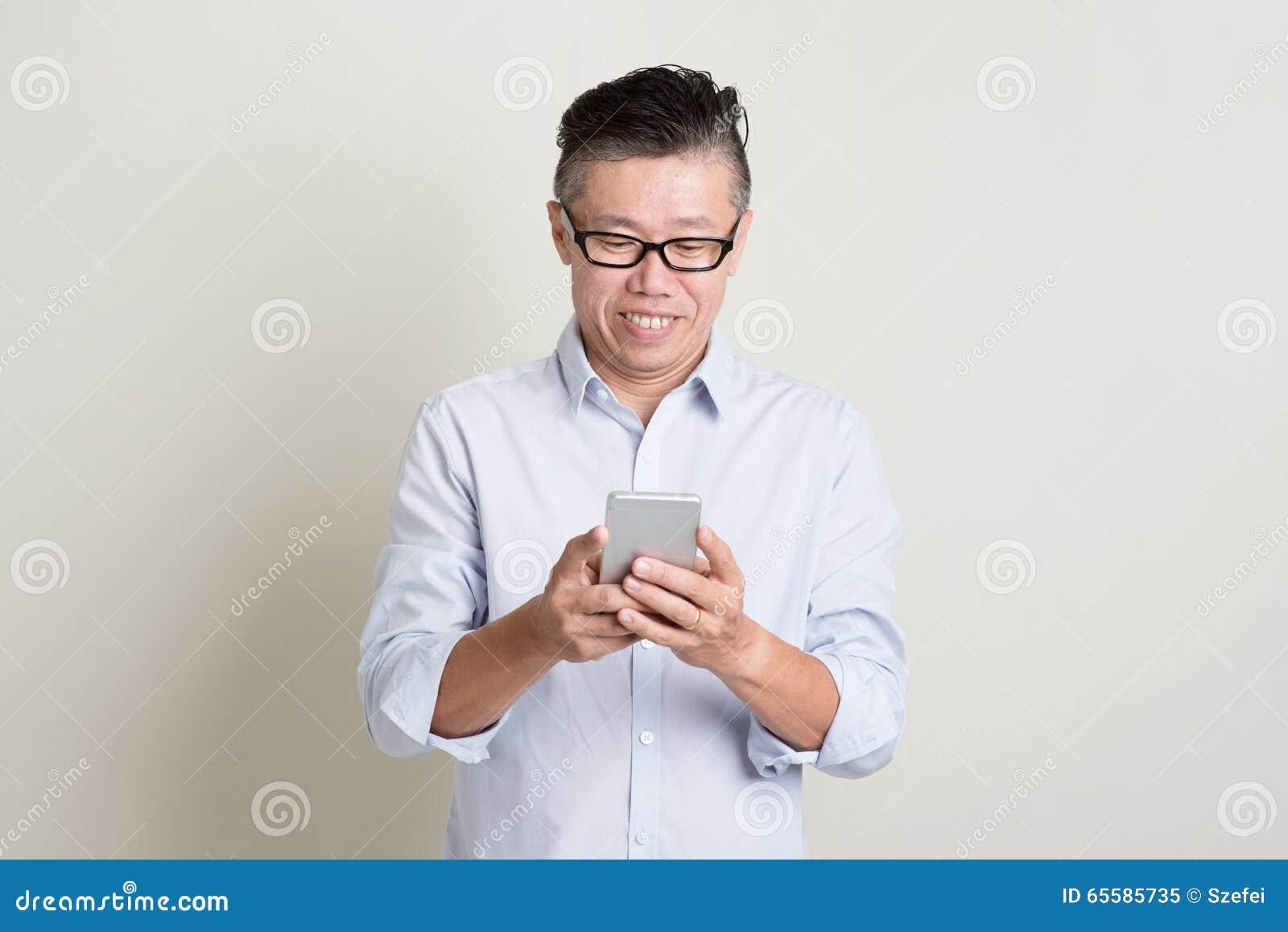 Homem asiático maduro que usa o smartphone