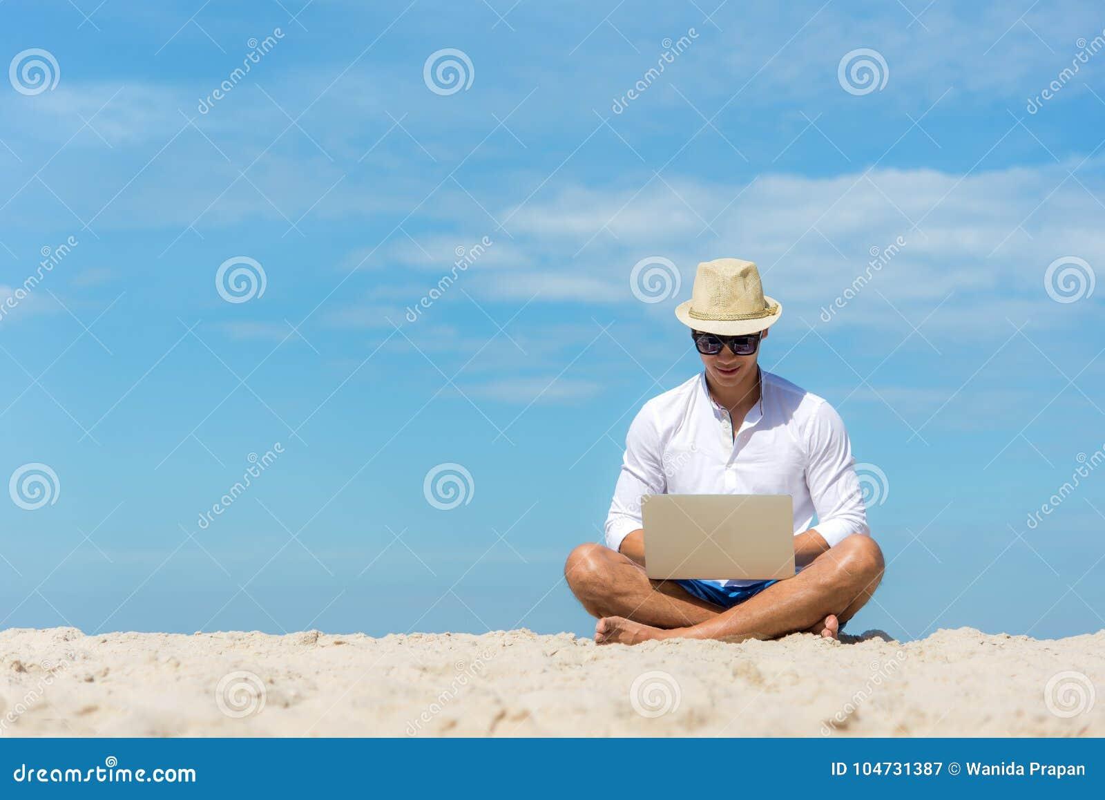 Homem asiático novo do estilo de vida que trabalha no portátil ao sentar-se na praia bonita, trabalho autônomo no verão do feriad