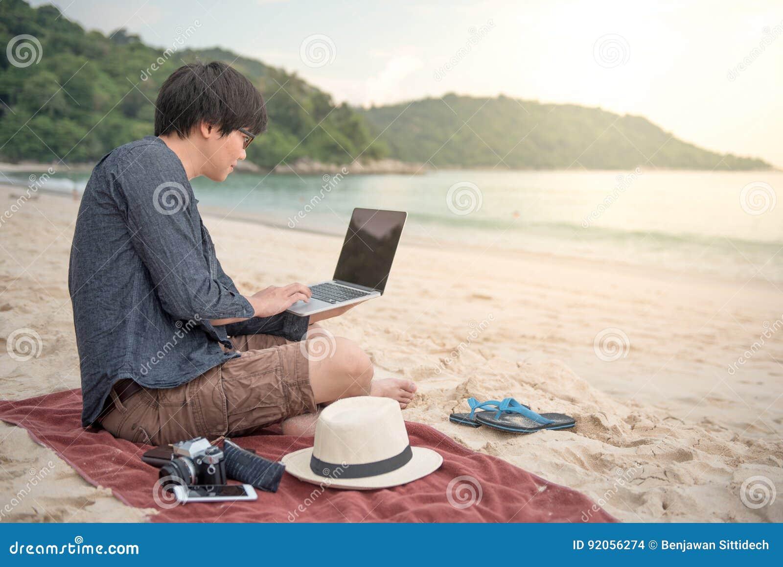 Homem asiático novo que trabalha com o portátil na praia