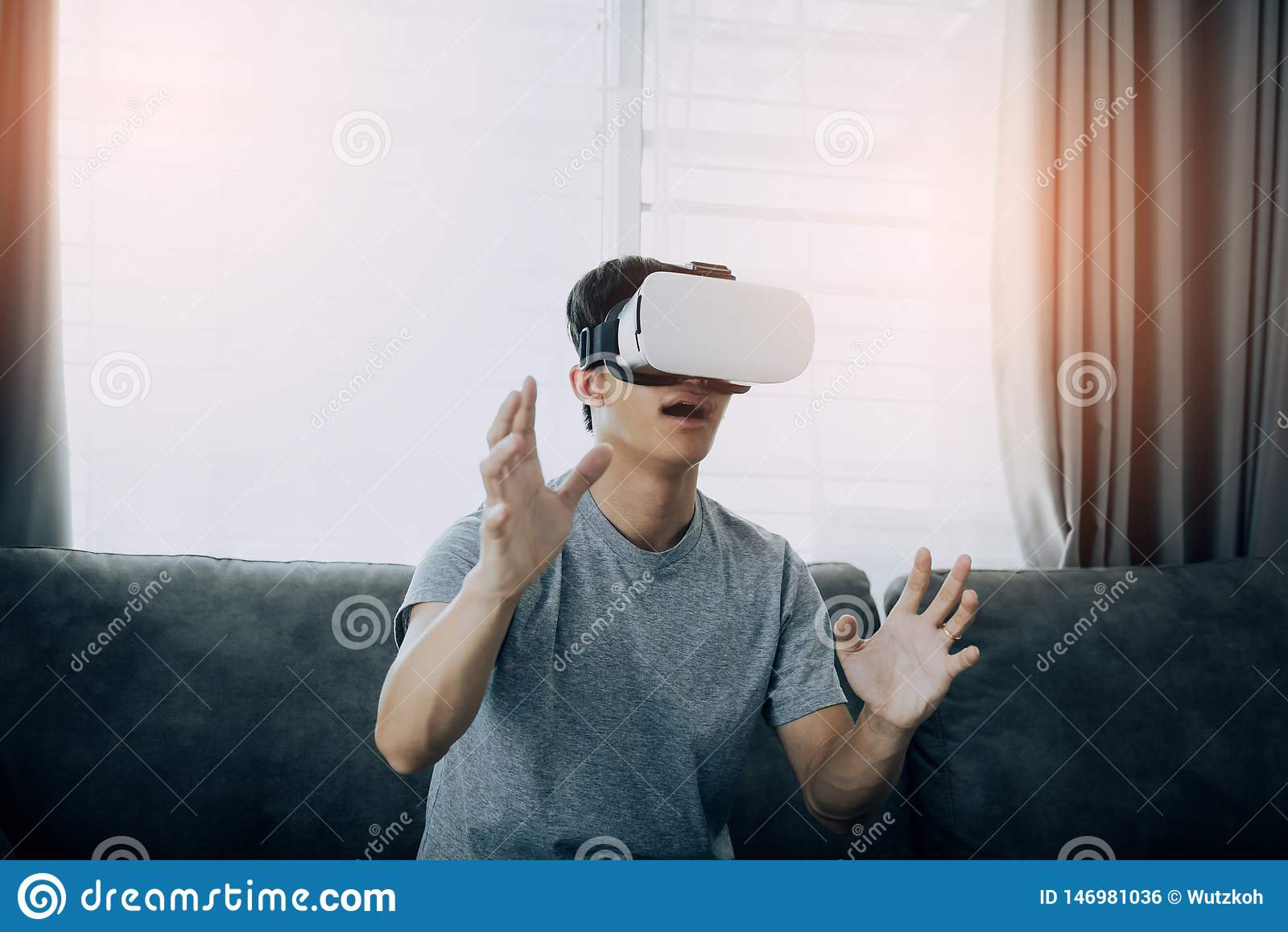 Homem asiático novo que veste vidros da realidade virtual na sala de visitas para admirar a realidade virtual