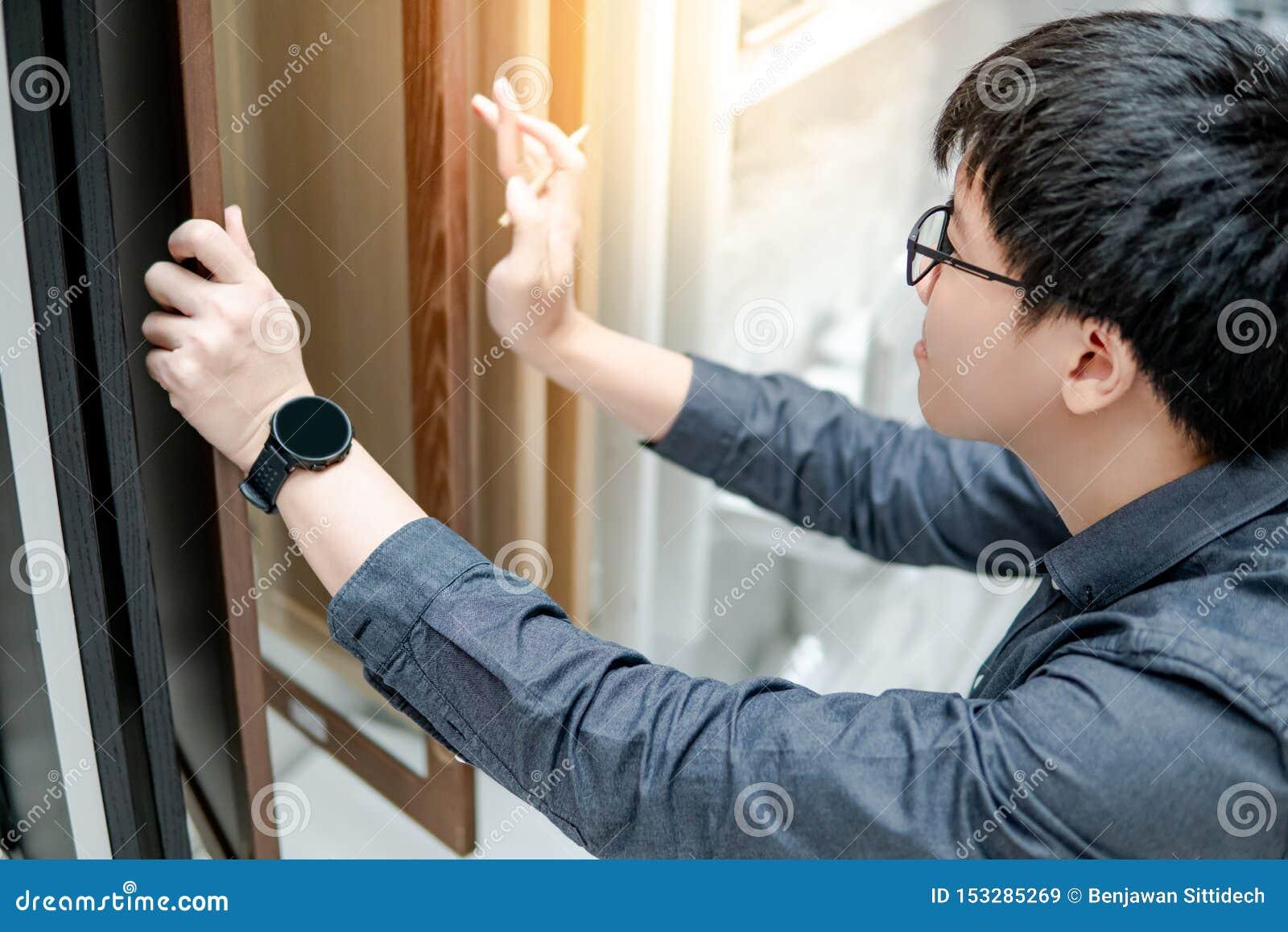 Homem asiático que escolhe materiais do armário ou da bancada
