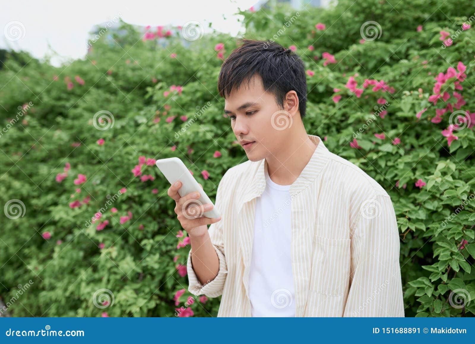 Homem asi?tico novo na roupa ocasional no dia de ver?o e no smartphone da utiliza??o para enviar sms