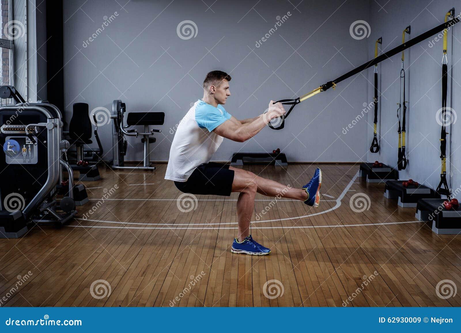 Homem atrativo durante o exercício com as correias da suspensão no Gym