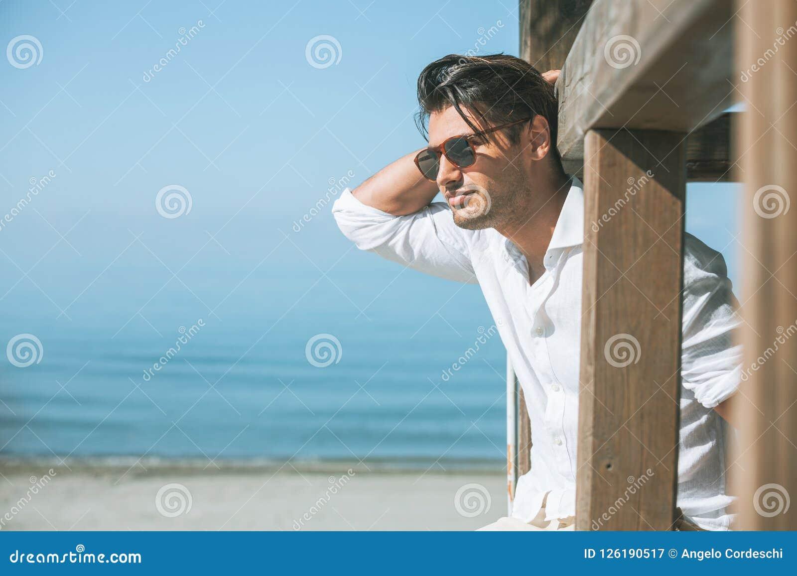 Homem atrativo novo com os óculos de sol que olham para fora sobre o mar durante o verão