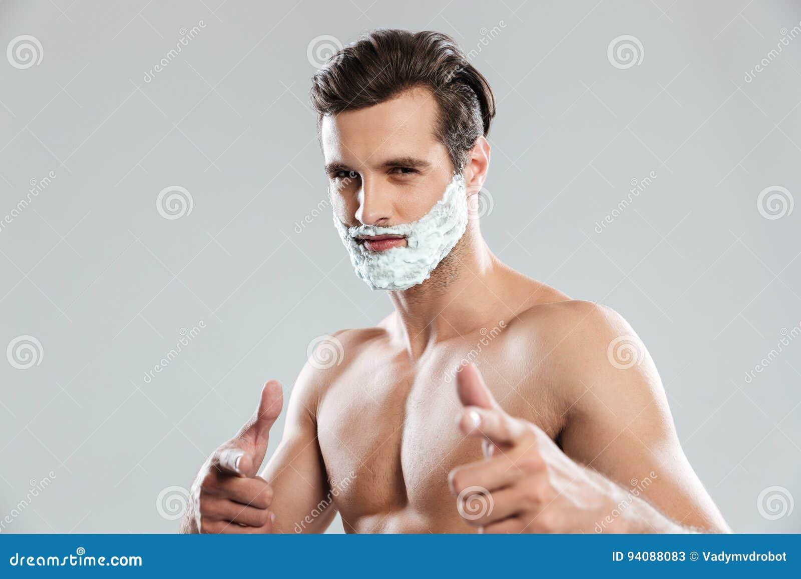 Homem atrativo novo com rapagem da espuma em apontar da cara