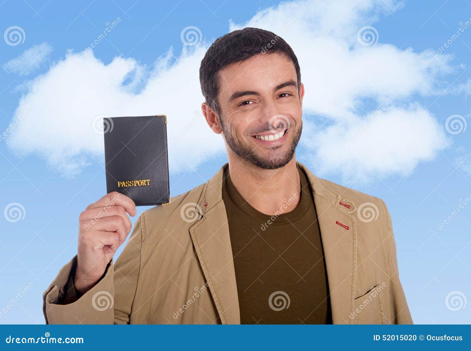 Homem atrativo novo do viajante que mantém o sorriso do passaporte feliz e seguro