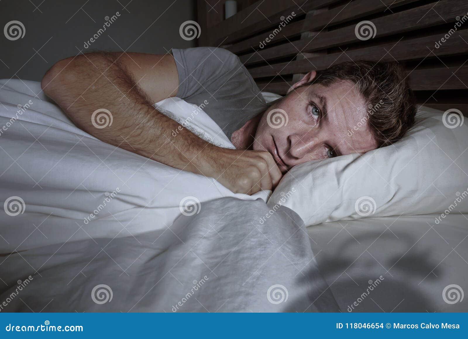 Homem atrativo novo preocupado agitado acordado na noite que encontra-se na cama sem sono tendo o sleepi de sofrimento comprimido