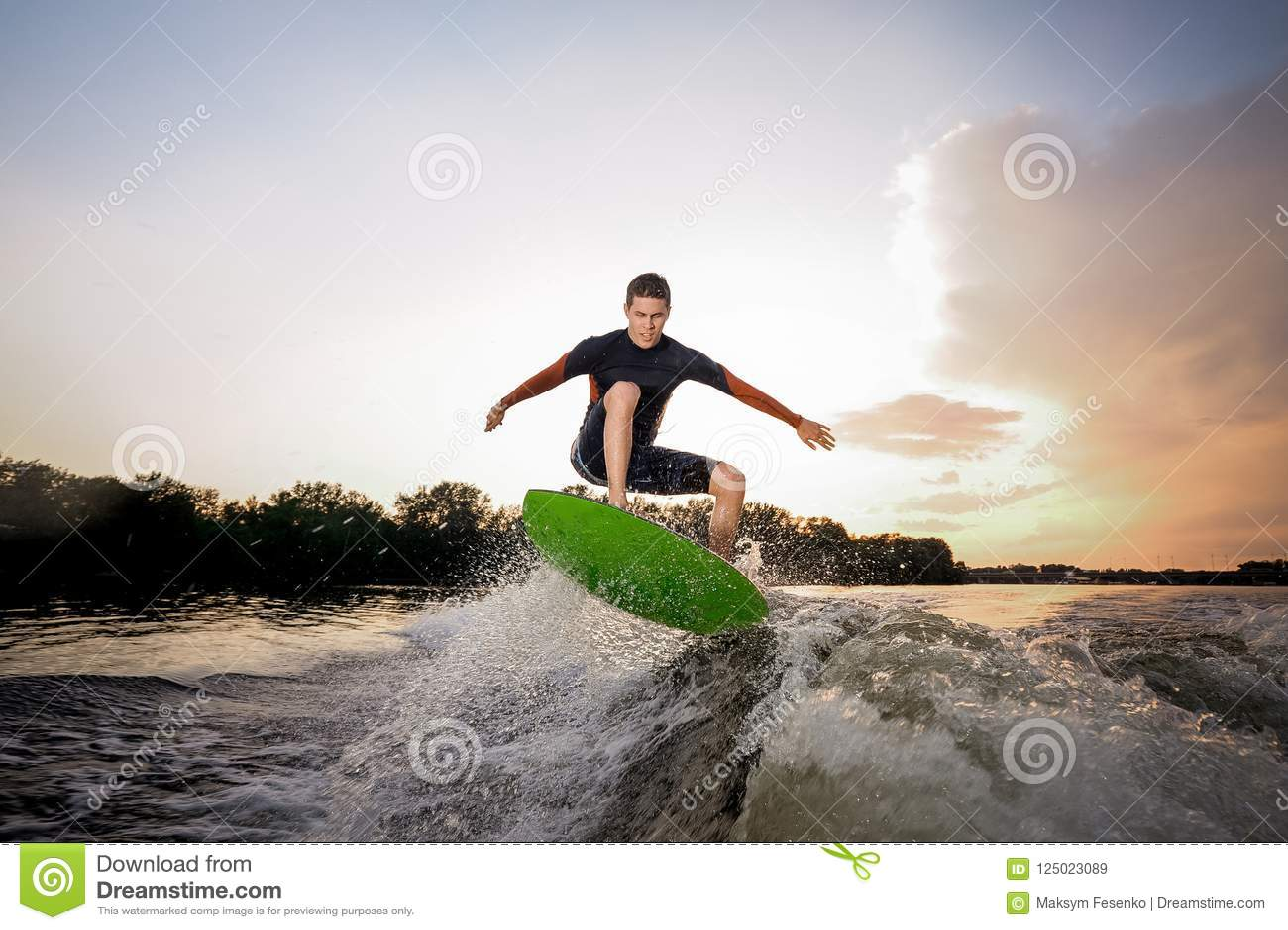 Homem atrativo novo que faz um salto no wakeboard verde