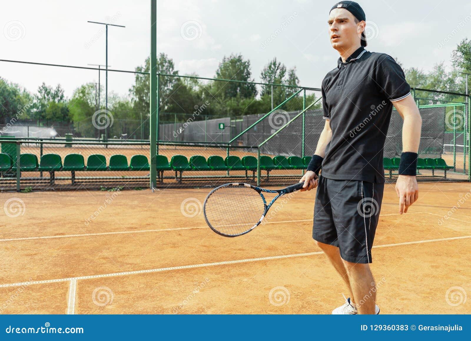 Homem atrativo novo que joga o tênis na corte e que espera o serviço da bola