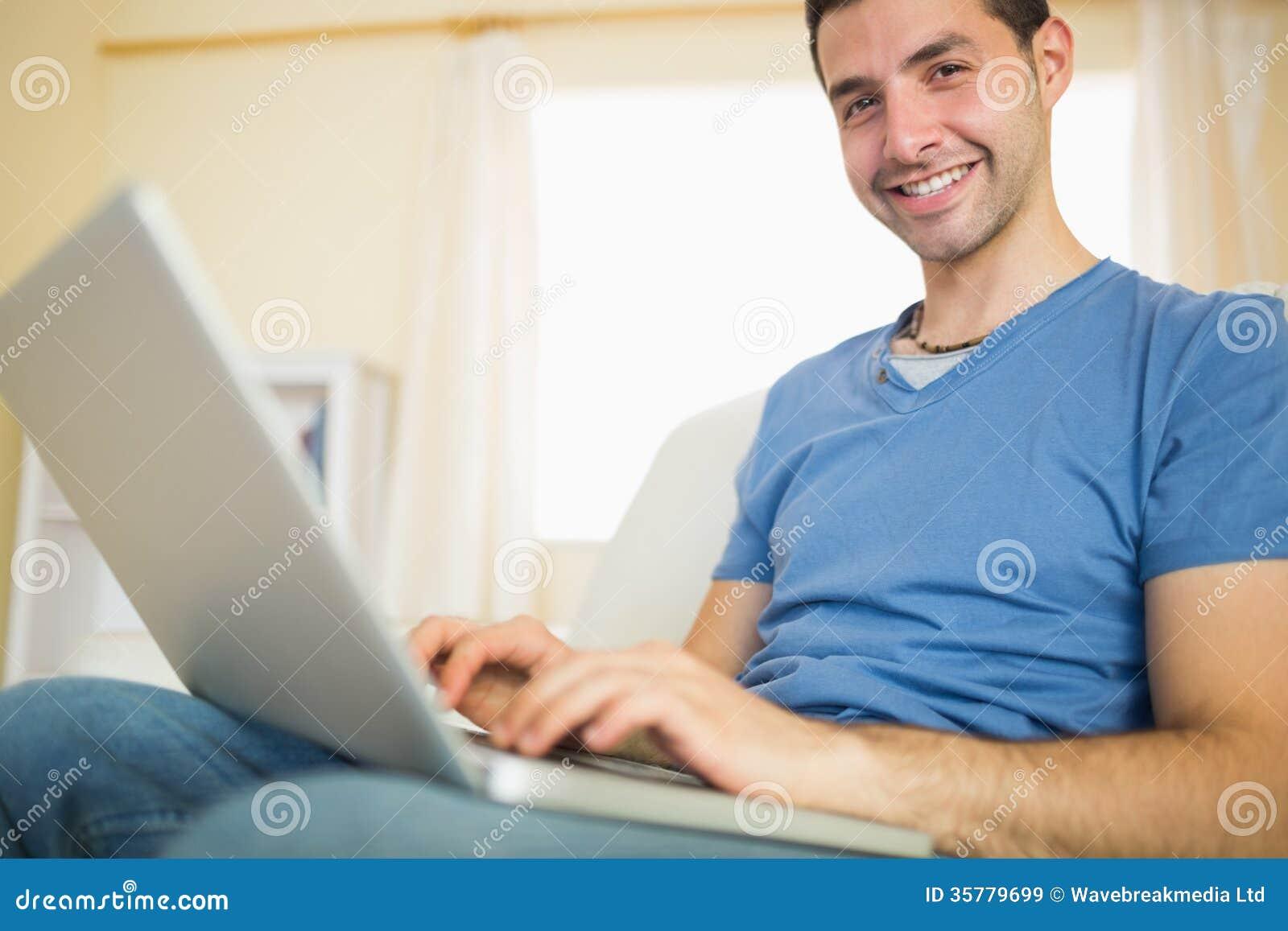 Homem atrativo ocasional que senta-se no sofá usando o portátil que olha a câmera