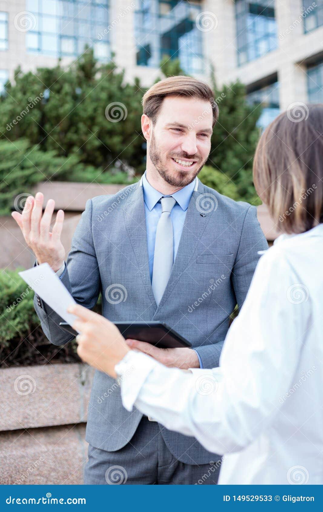 Homem bem sucedido e executivos fêmeas que falam na frente de um prédio de escritórios, tendo uma reunião e discutindo