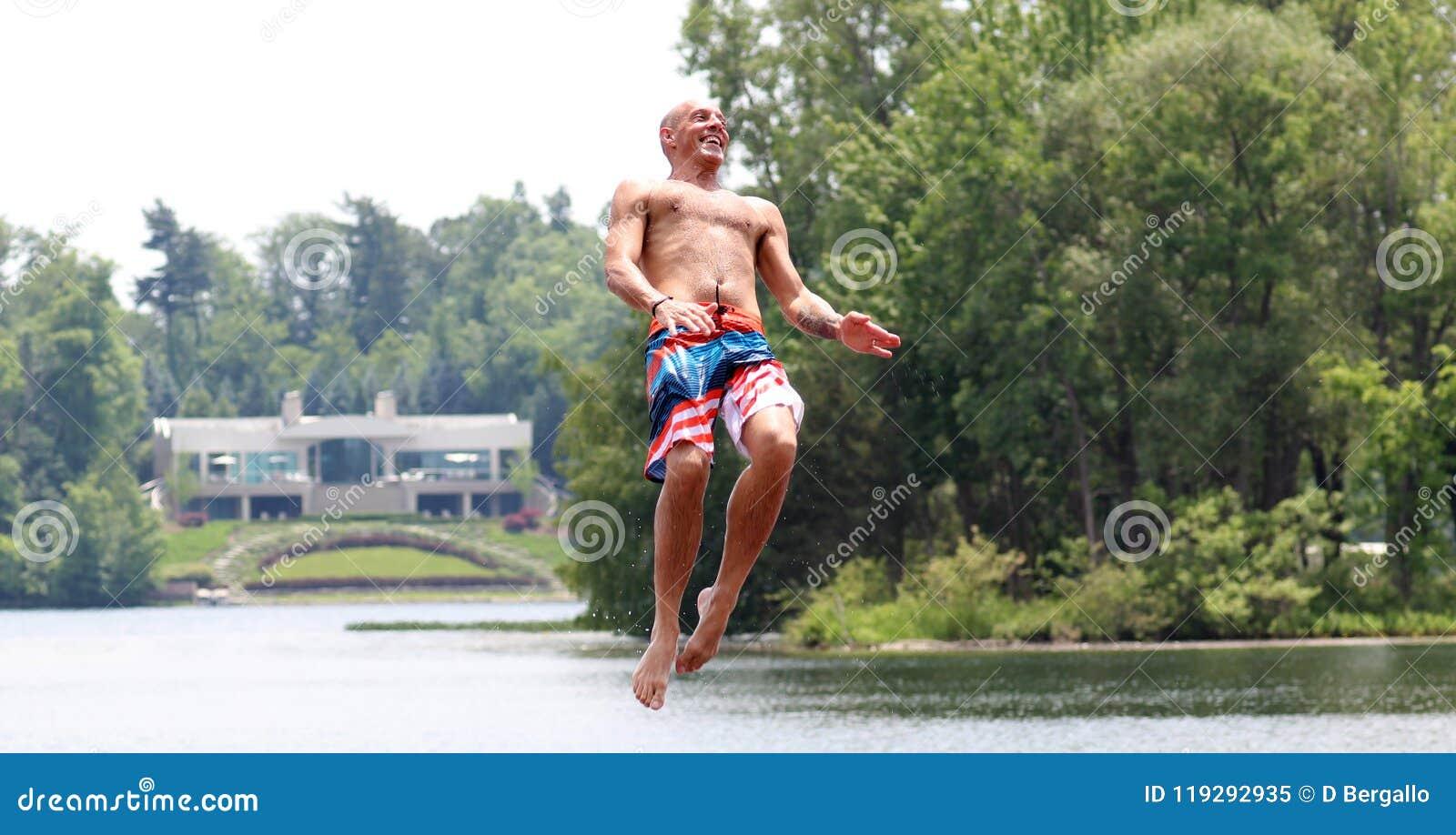 Homem bonito considerável que salta em um trampolim da água que flutua em um lago em Michigan durante o verão