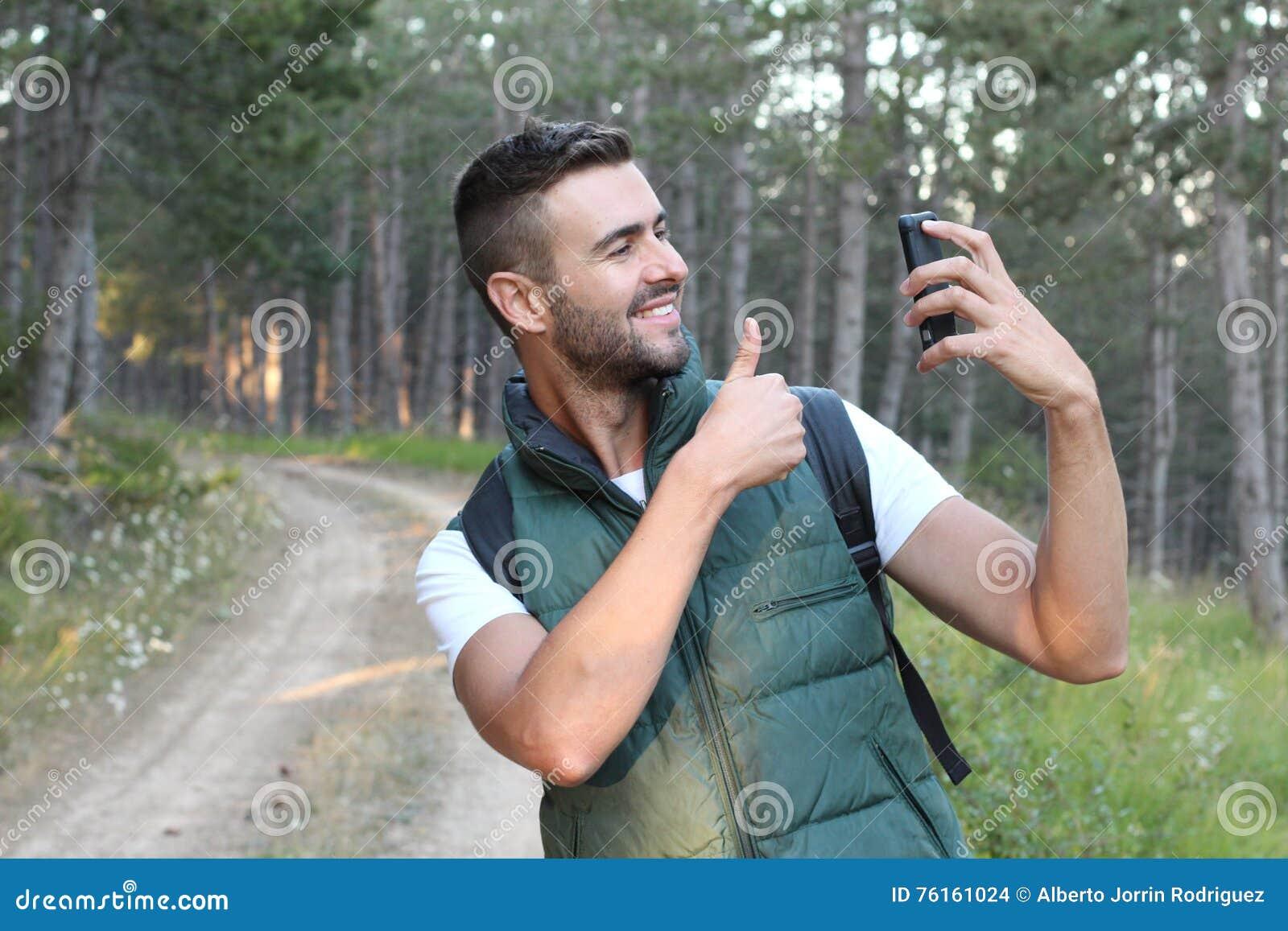 Homem bonito feliz que faz a foto do selfie no smartphone e que mostra o polegar acima sobre o fundo da natureza da floresta ou d