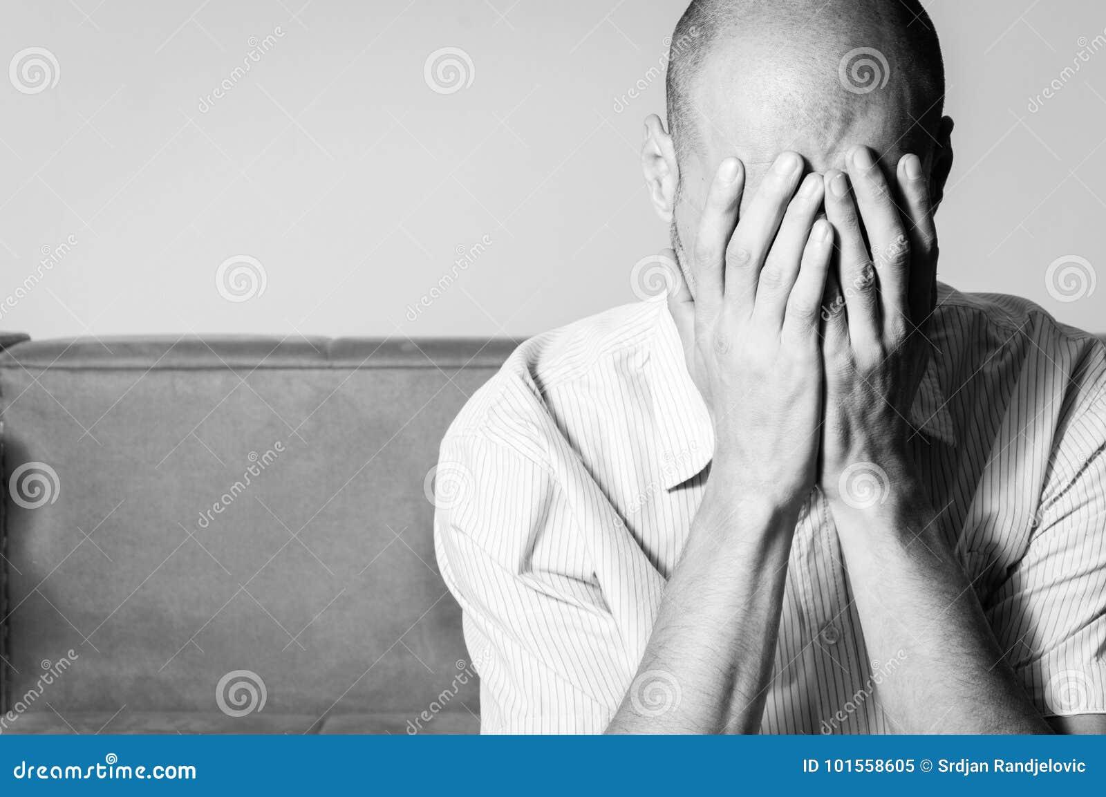 Homem calvo novo na camisa que sente tampa comprimida e miserável sua cara com seus mãos e grito em sua sala preto e branco