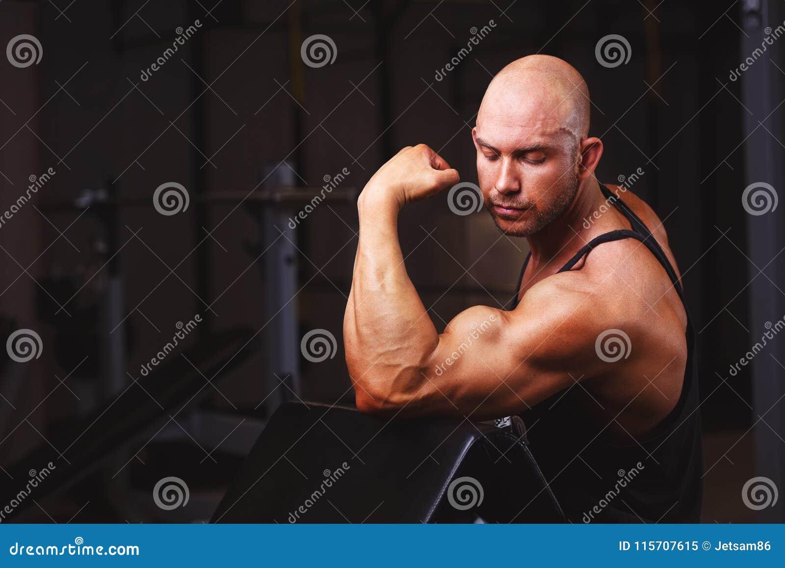 Homem calvo rasgado forte que demonstra os músculos grandes no gym Esporte,
