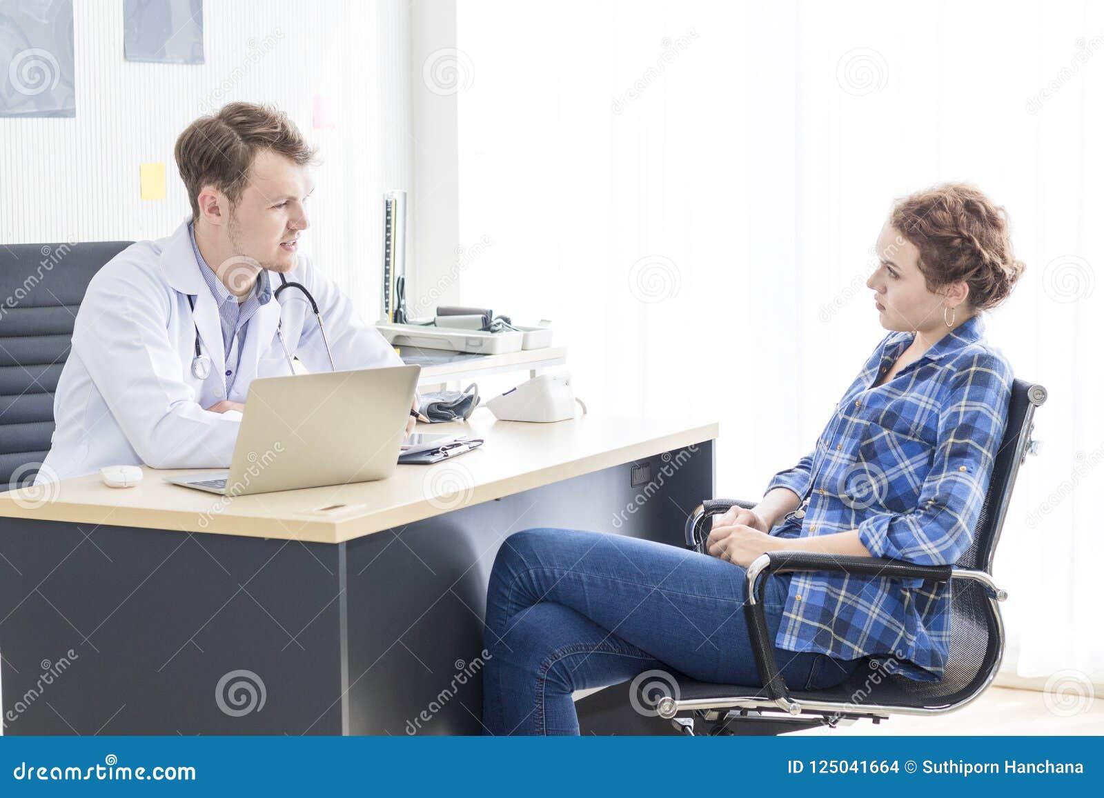 Homem caucasiano dos profissionais médicos que tranquiliza e que fala com o paciente do esforço da jovem mulher