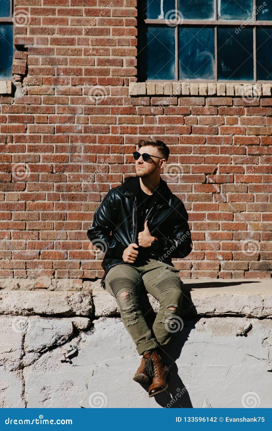 Homem caucasiano Guy Walking da forma moderna atrativa nova, sentando-se, sorrindo, e rindo fora do tijolo abandonado velho urban