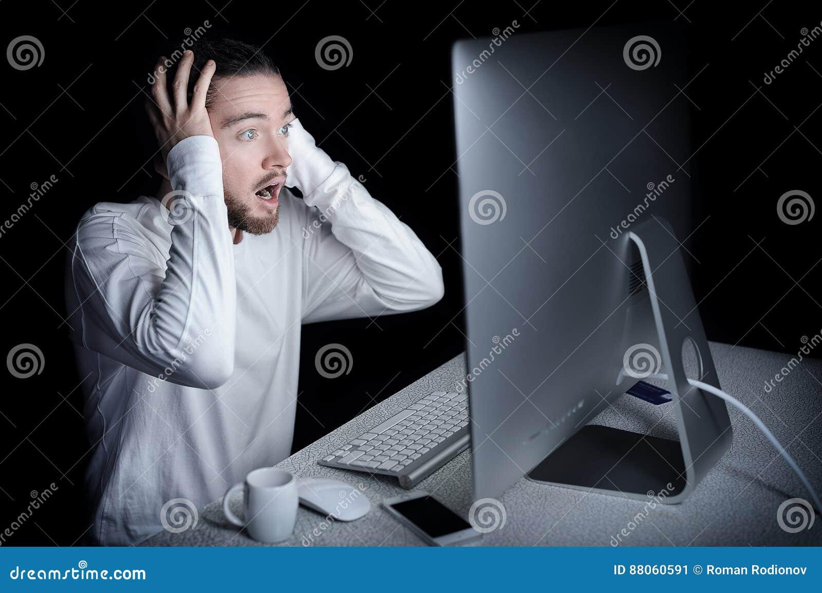 Homem chocado com seu computador