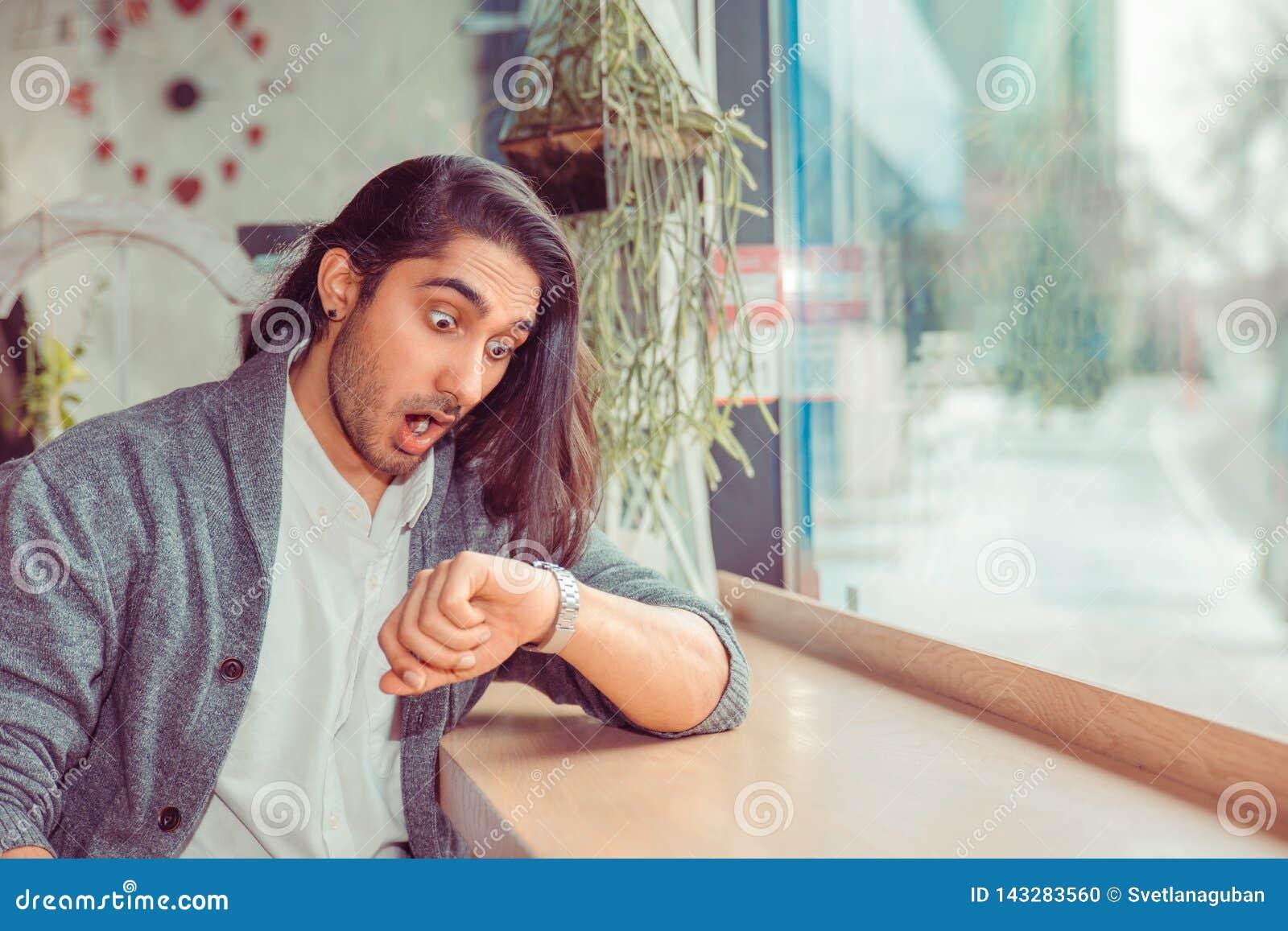 Homem chocado que olha ao relógio de pulso pelo tempo, estando atrasado