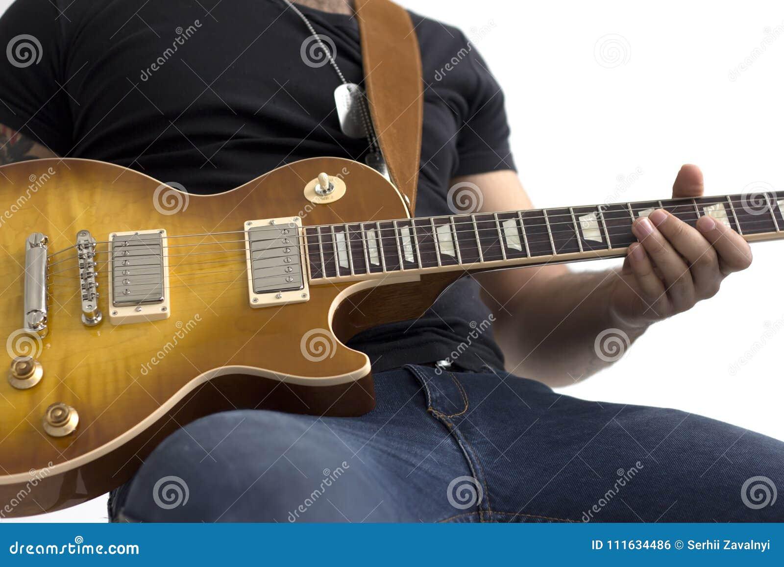 Homem com assento da guitarra elétrica isolado sobre o branco