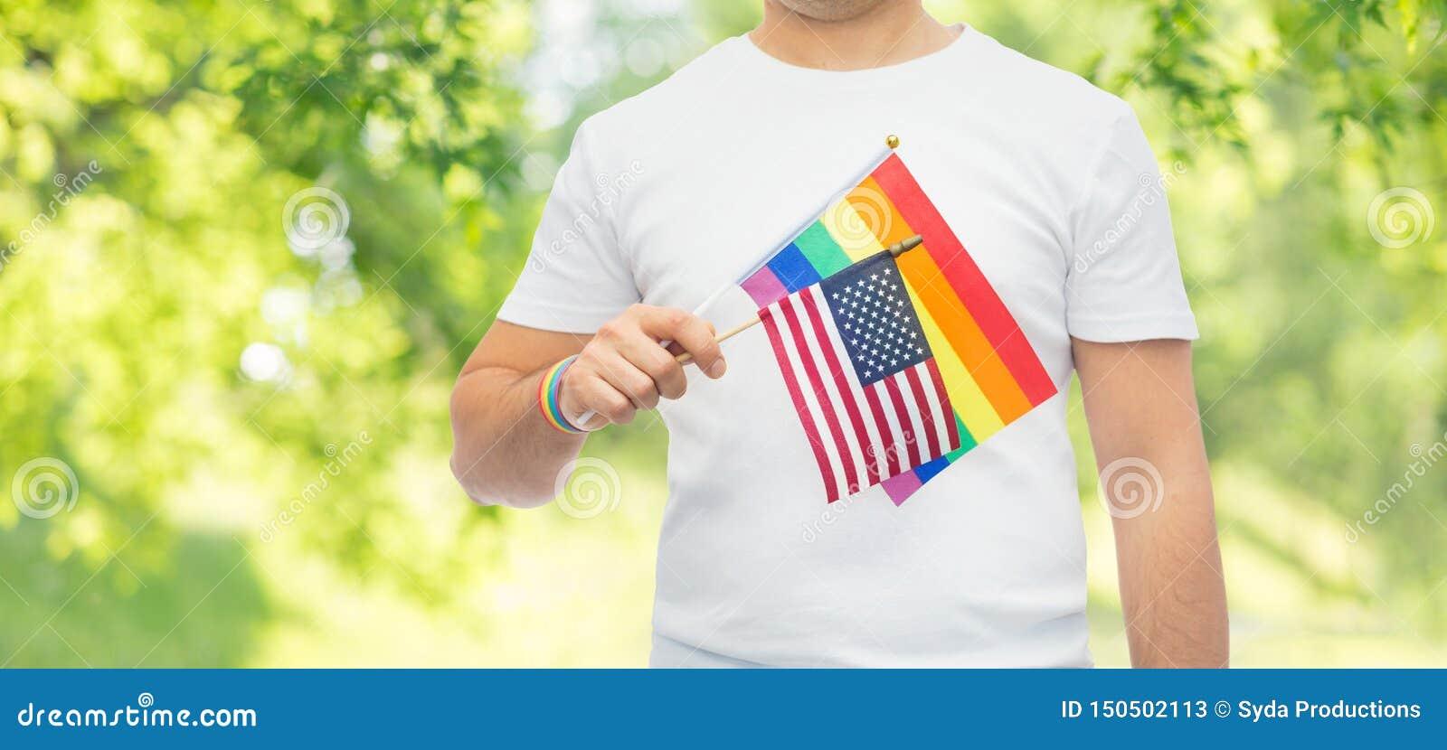Homem com a bandeira e o punho do arco-?ris do orgulho alegre