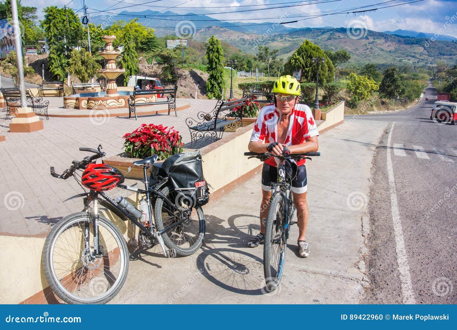 Homem, com a bicicleta na estrada na Guatemala