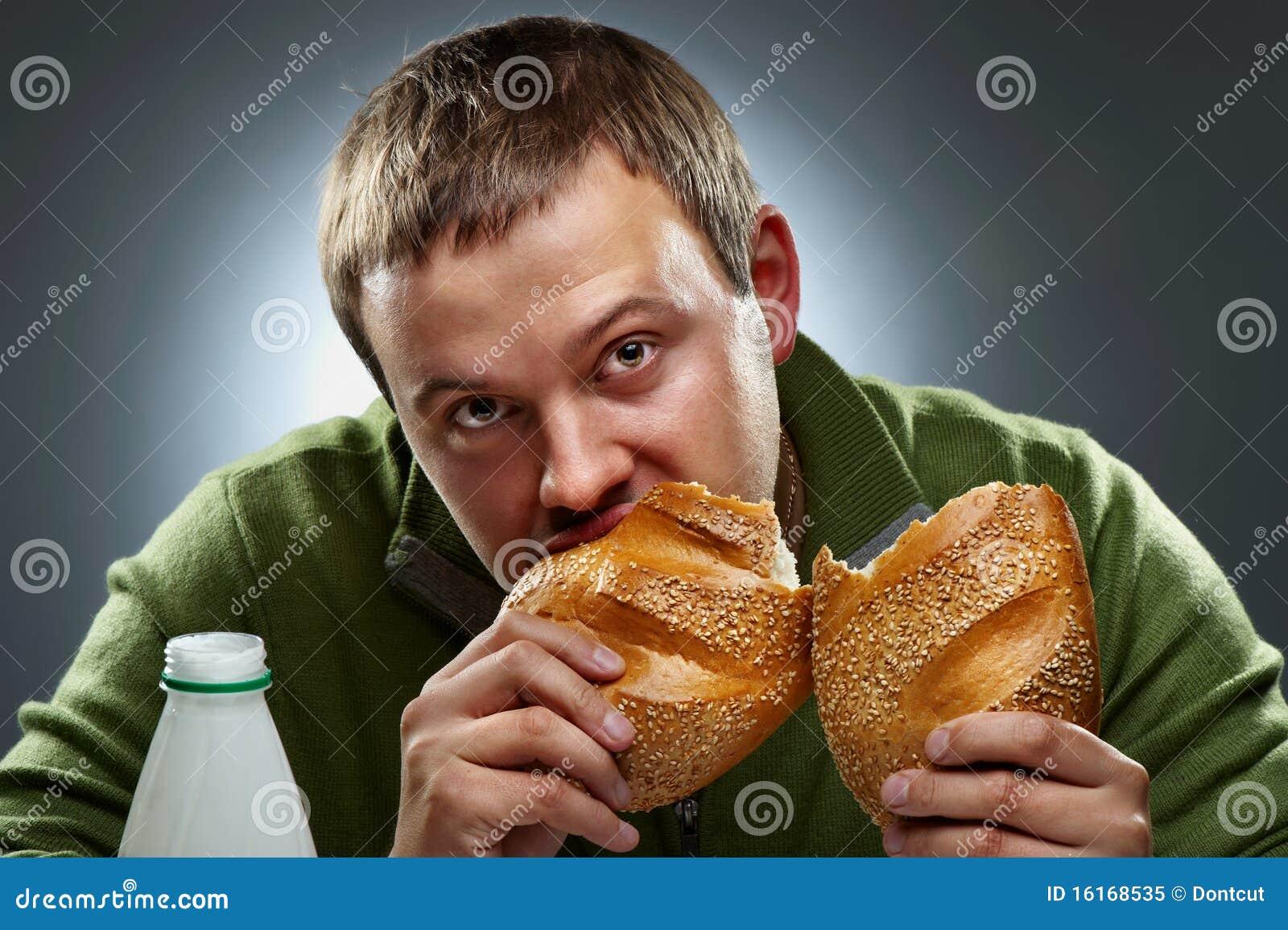 Homem com fome com a boca cheia do pão