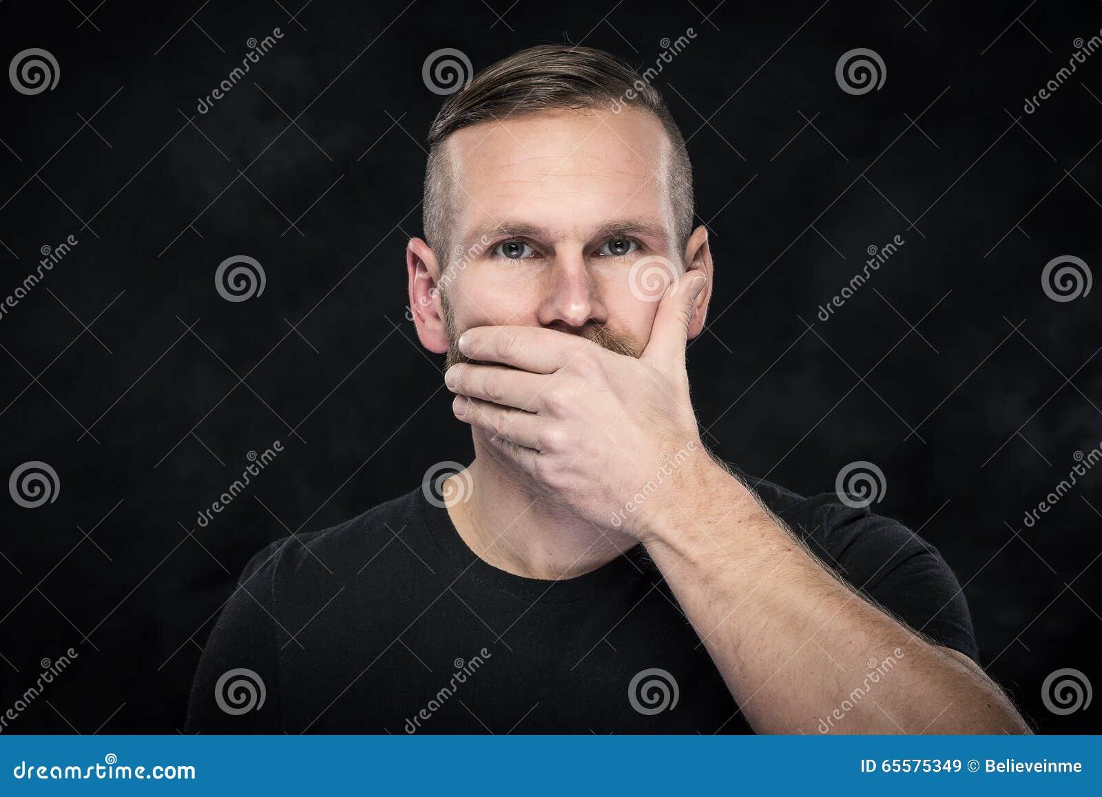 Homem com a mão que cobre sua boca