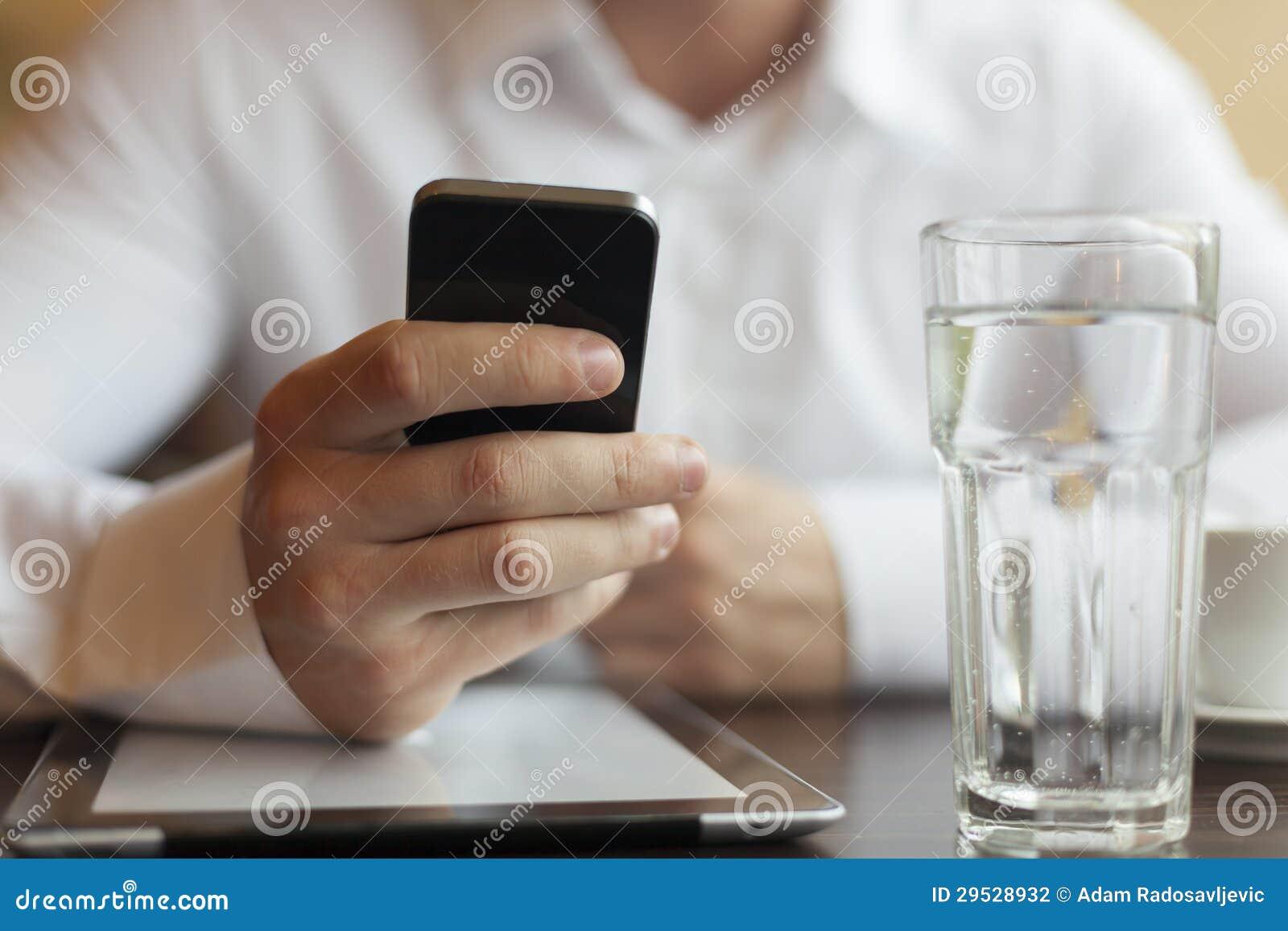 Homem com o computador do smartphone e da tabuleta no restaurante