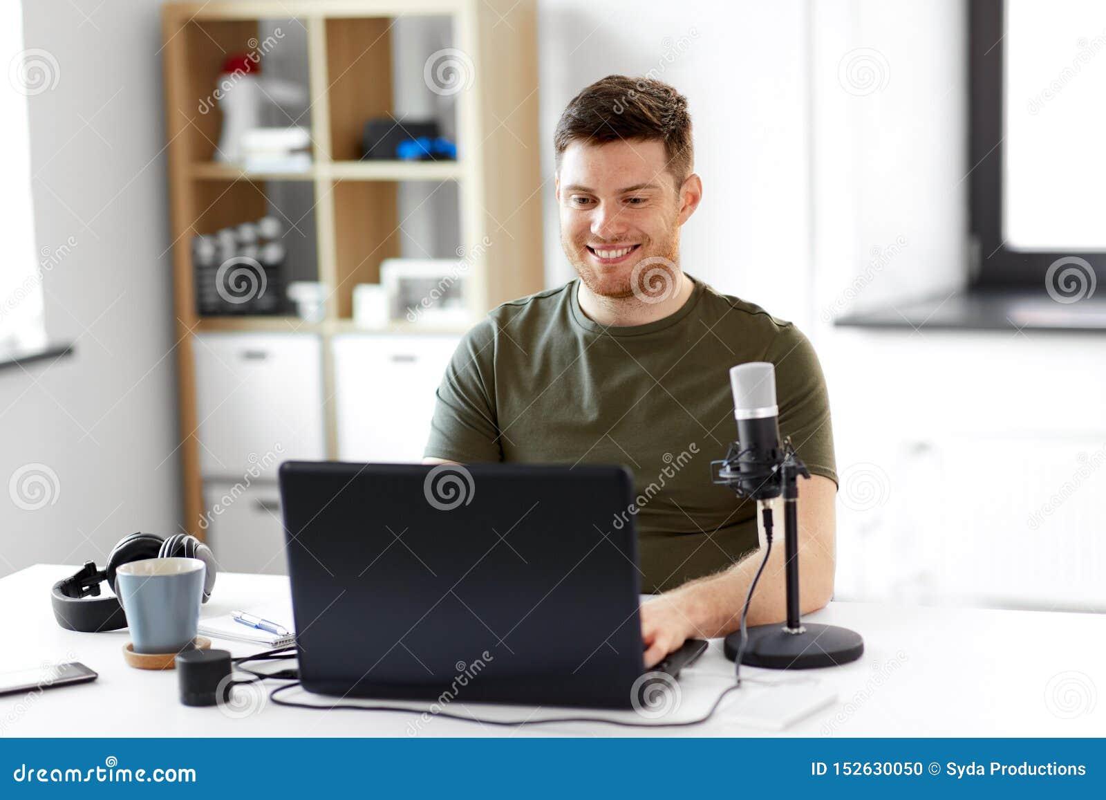 Homem com o escrit?rio do port?til e do microfone em casa