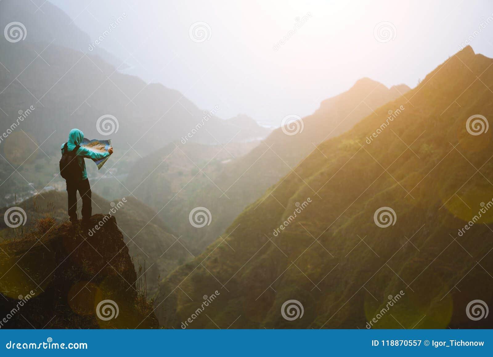 Homem com o mapa que fica sobre a rocha da montanha com opinião lindo do panorama sobre escalas de montanha alta e profundamente
