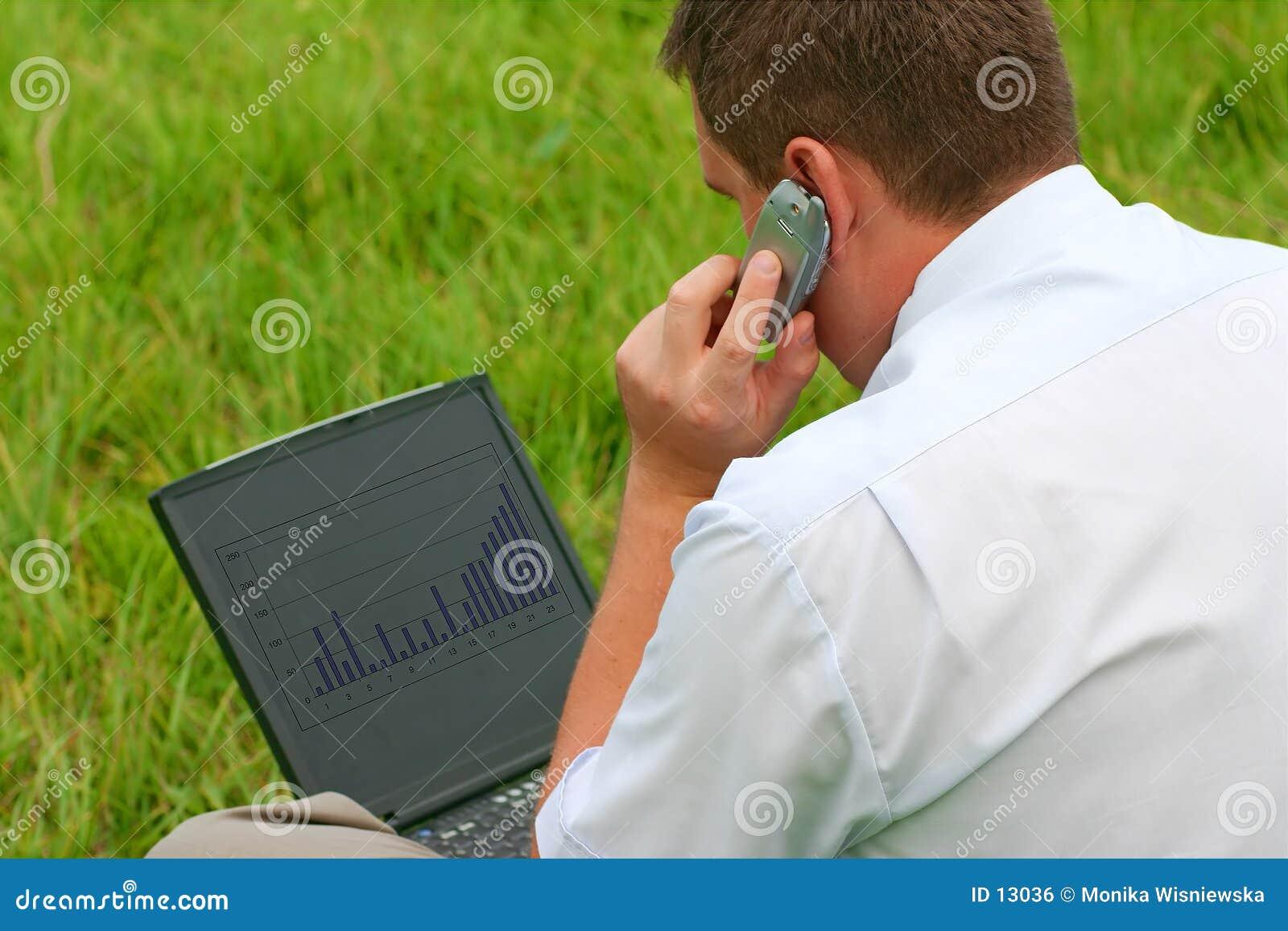 Homem com o portátil que senta-se na grama