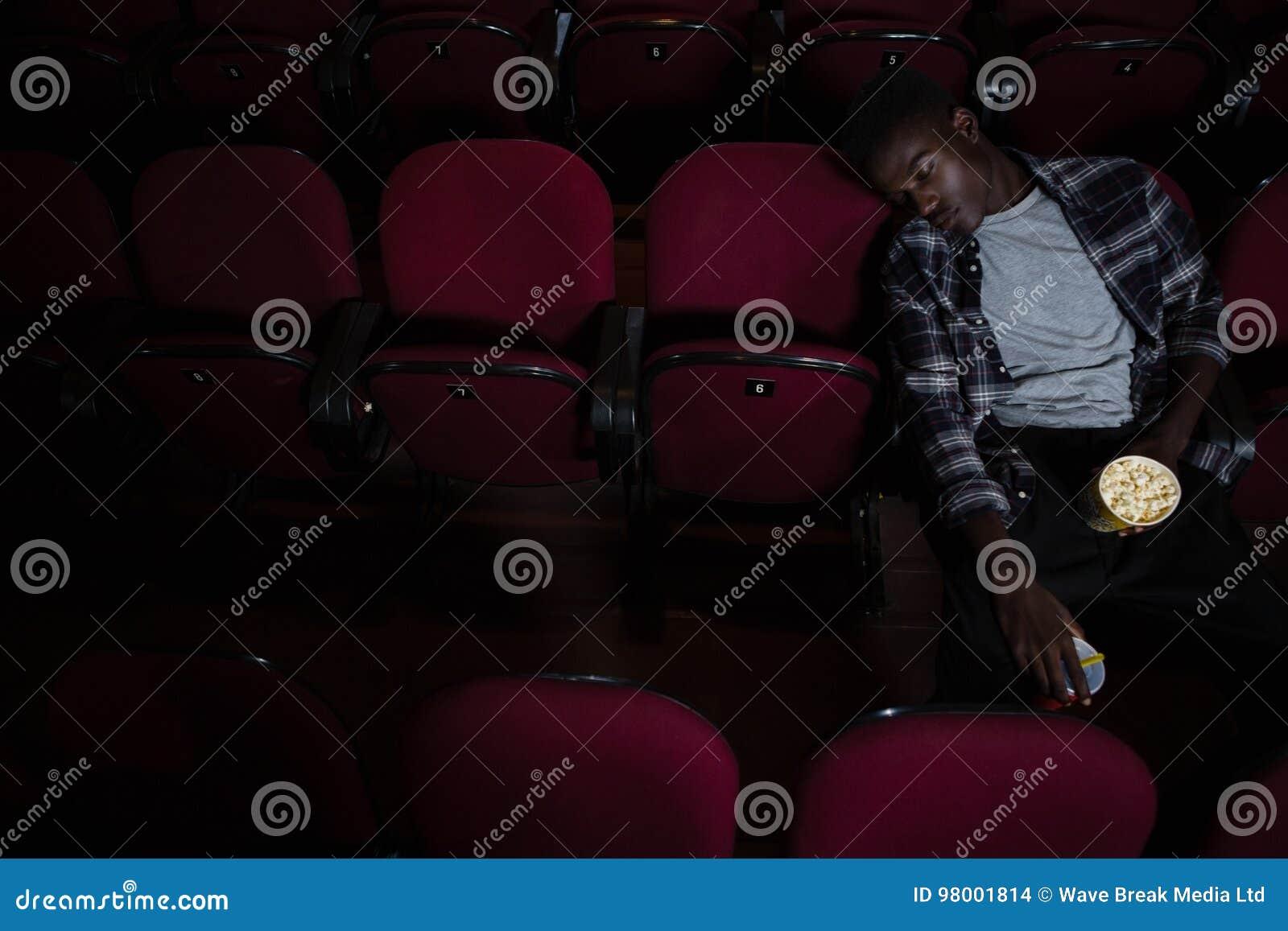 Homem com pipoca que dorme no teatro