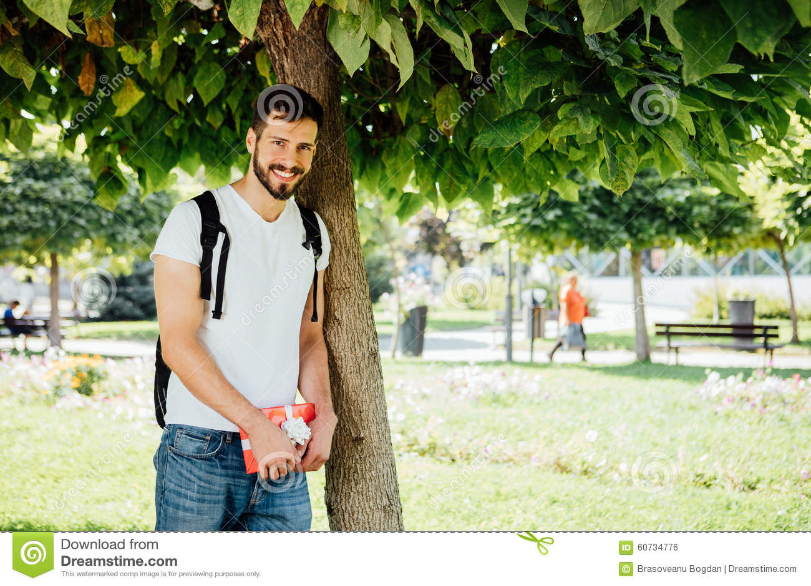 Homem com trouxa e um presente ao lado de uma árvore