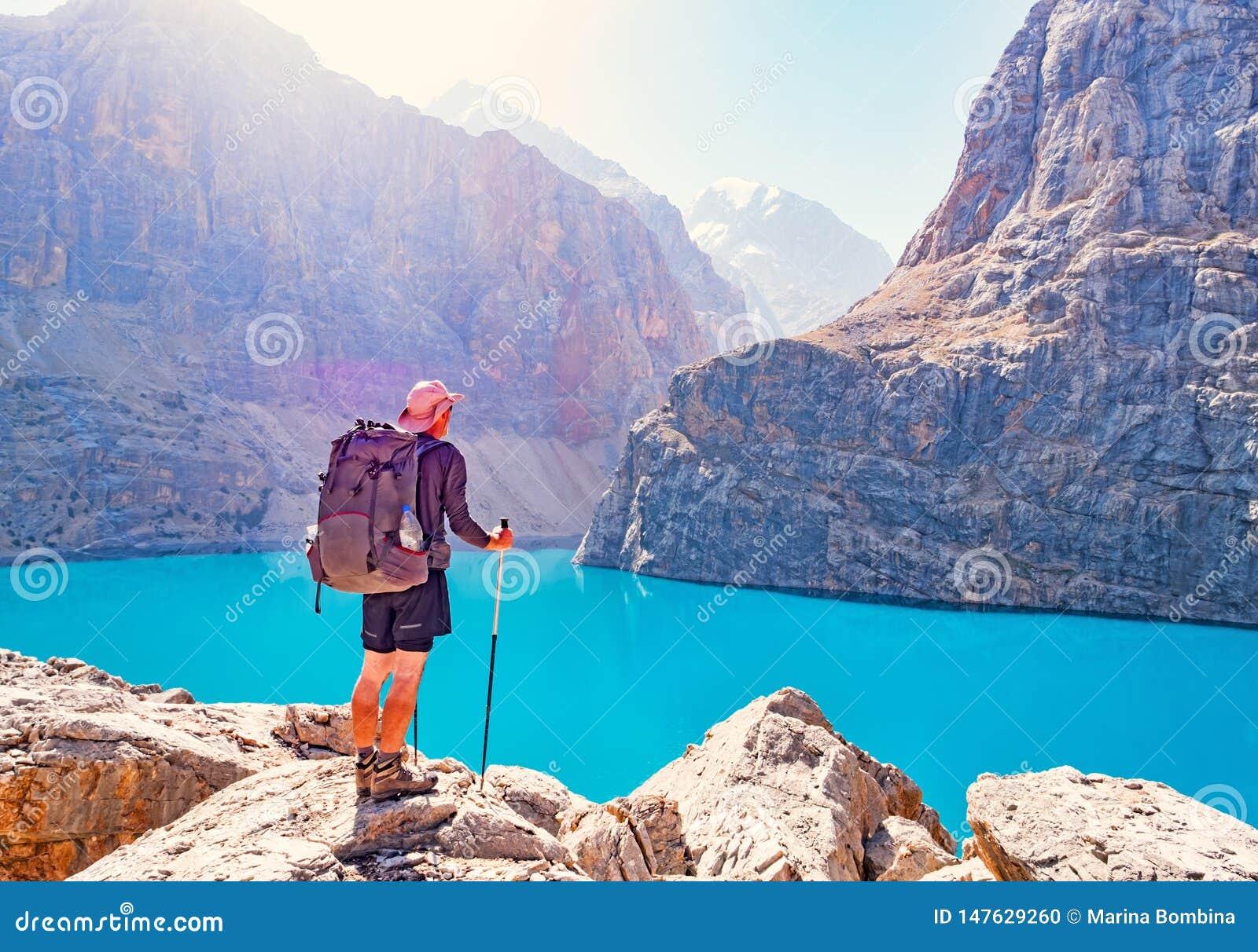 Homem com a trouxa perto do lago Alo grande no fundo da montanha rochosa Fann Mountains
