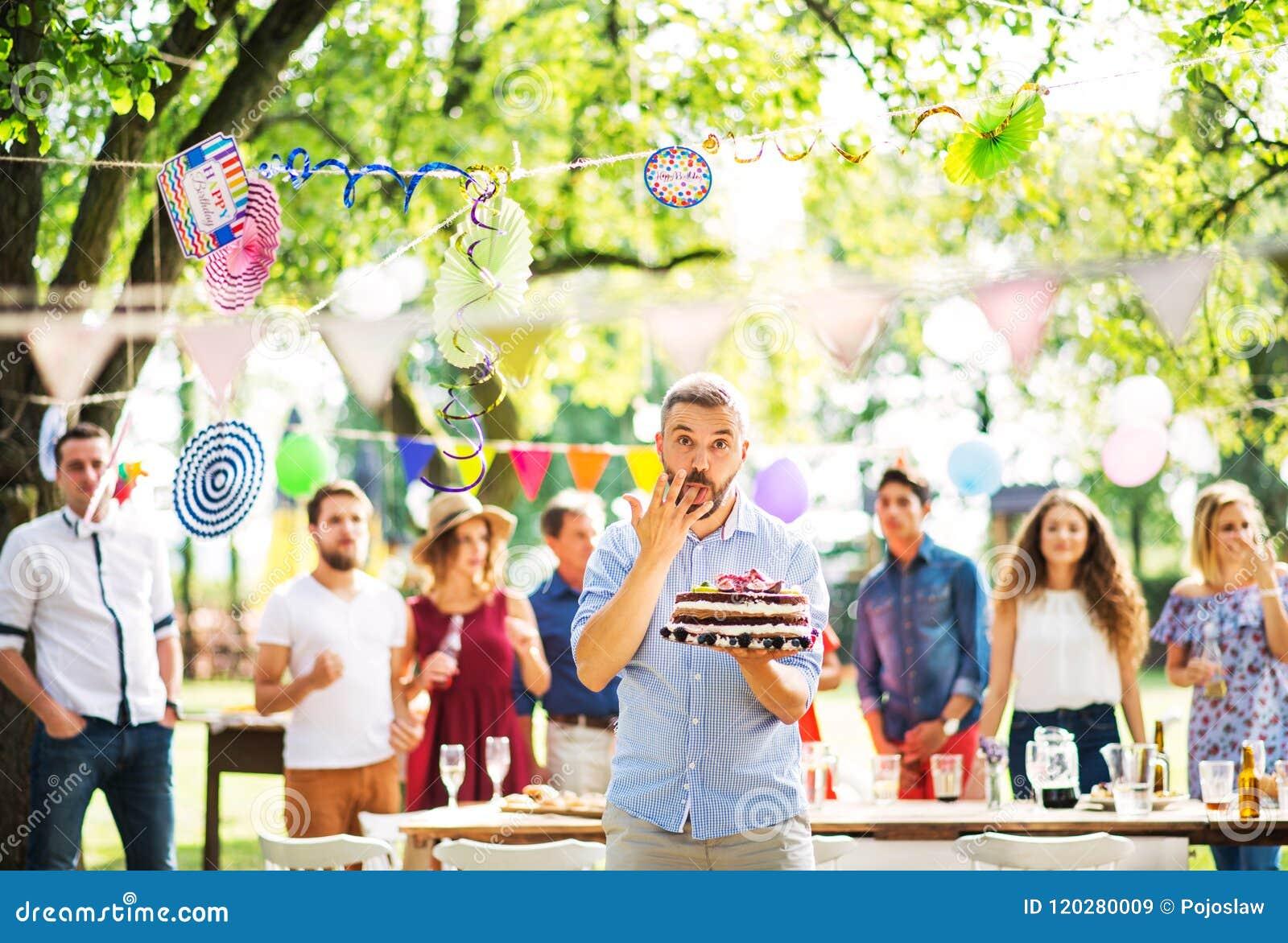 Homem com um bolo em uma celebração de família ou em um partido de jardim fora, lambendo seu dedo