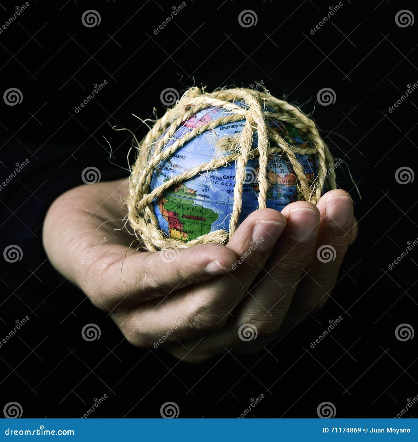 Homem com um globo do mundo amarrado com corda
