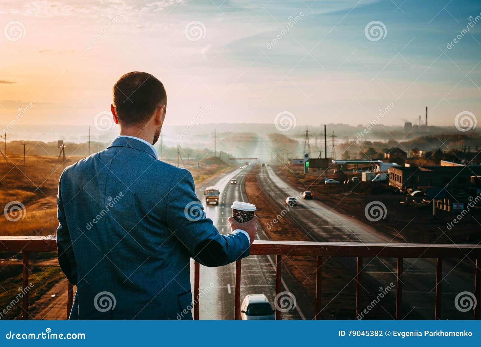 Homem com a xícara de café na ponte Amanhecer, o nascer do sol, a estrada desaparece na distância