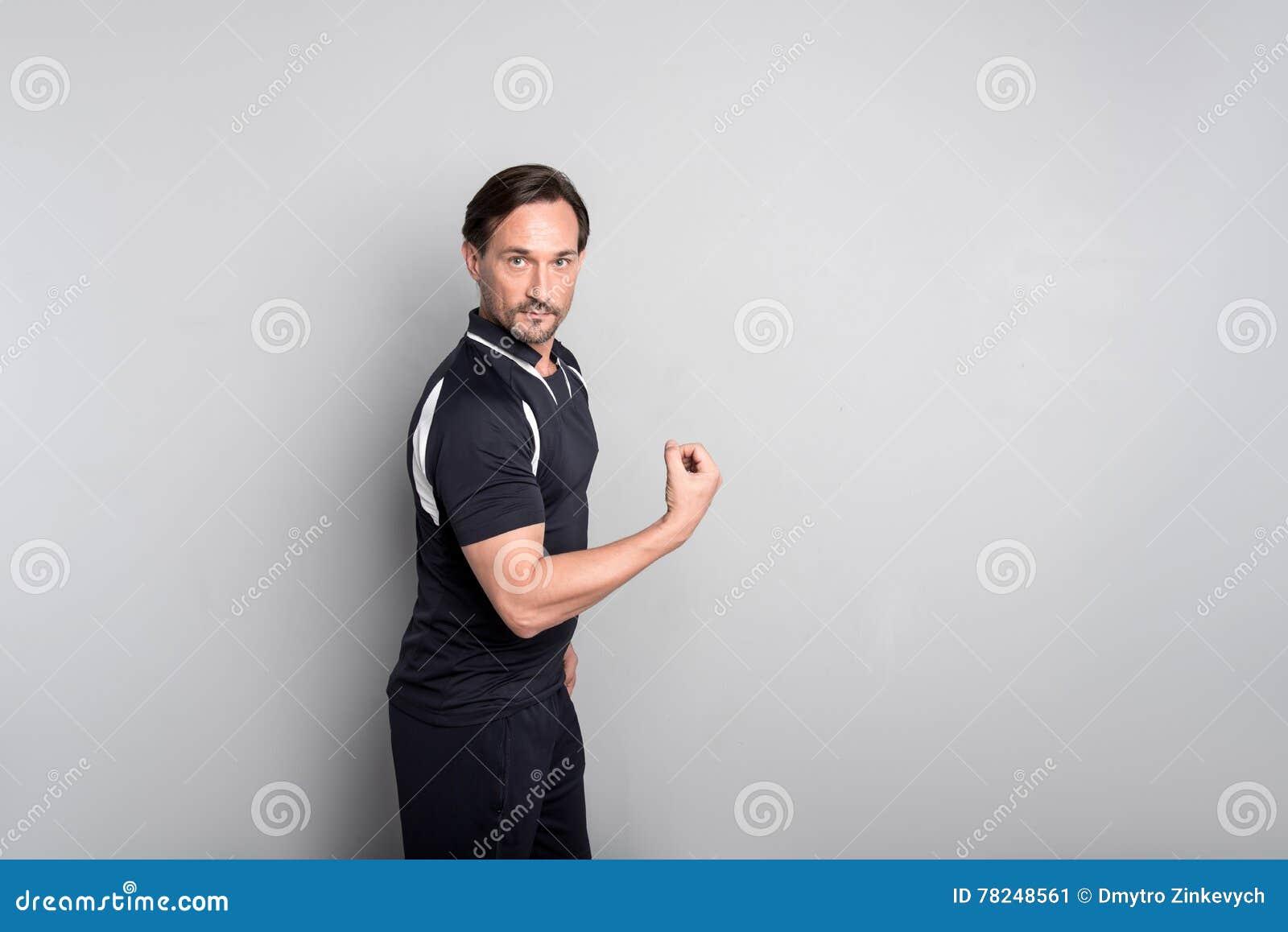 Homem considerável agradável que mostra sua força