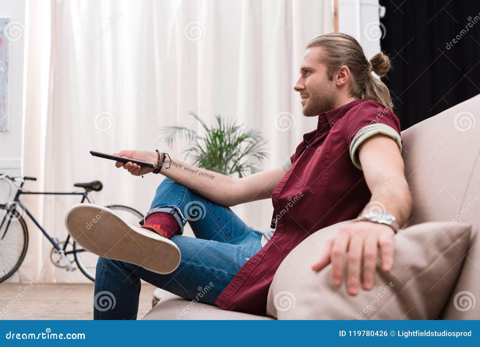 Homem considerável com a tevê de observação de controle remoto