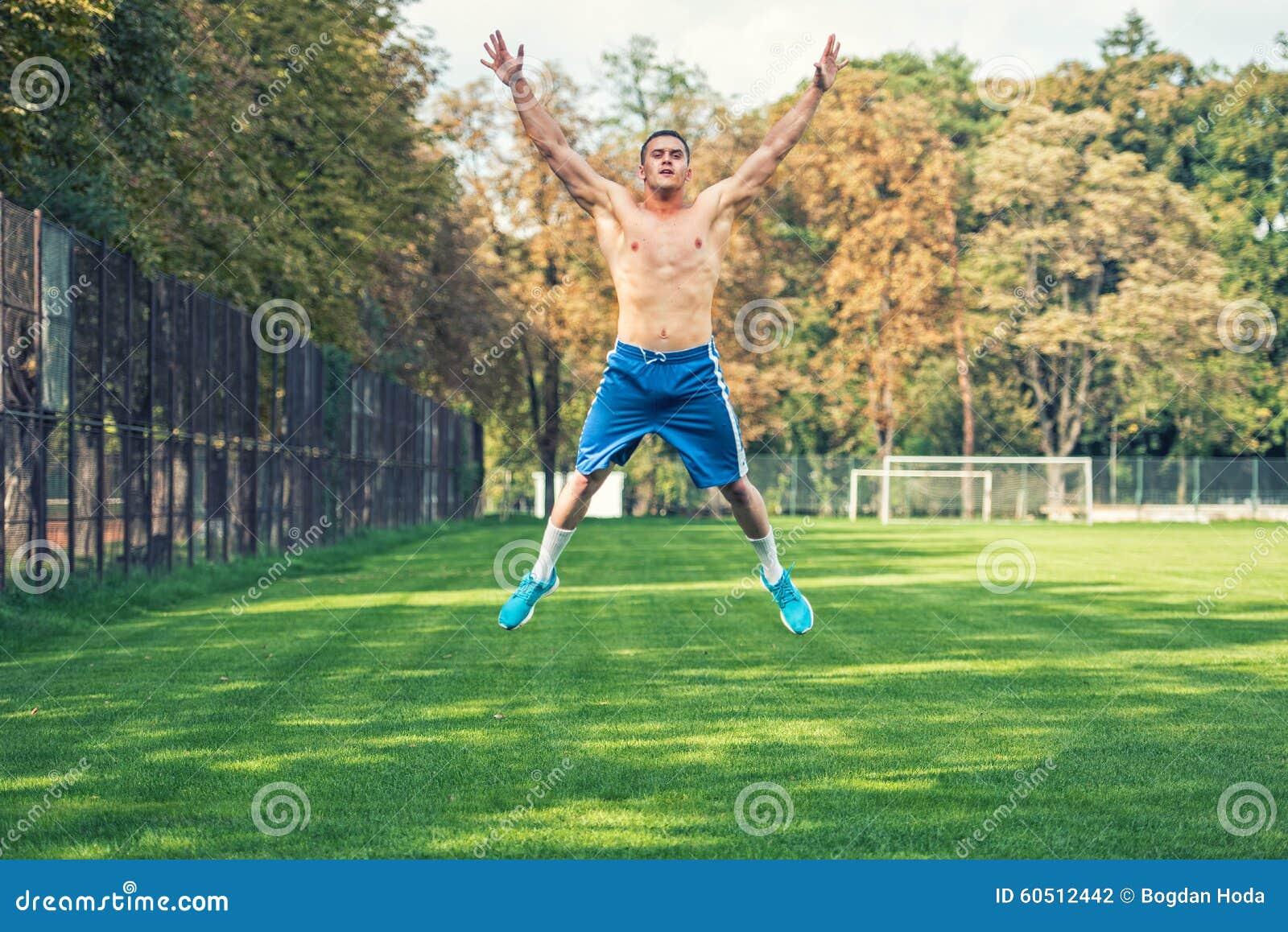 Homem considerável descamisado que dá certo no parque, treinamento apto da cruz Homem atlético que salta e que faz os exercícios