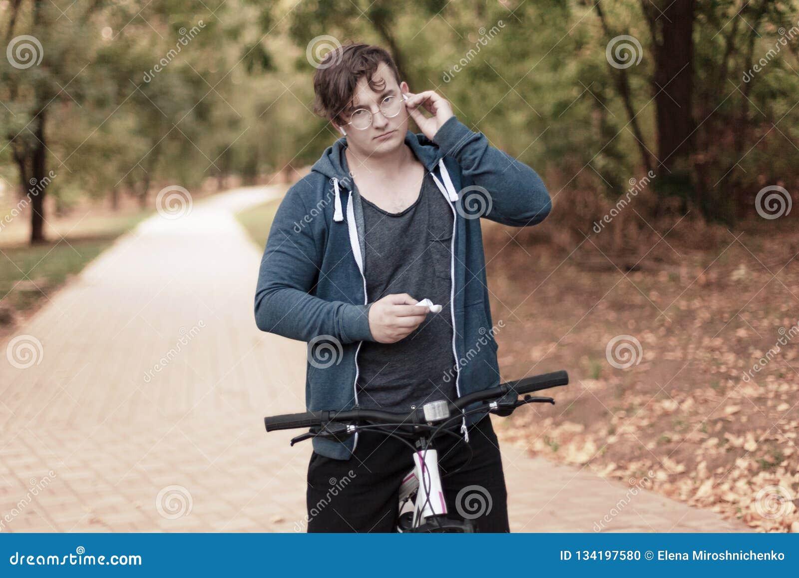 Homem considerável do caucasia com monóculos redondos e os fones de ouvido que bicycling no parque