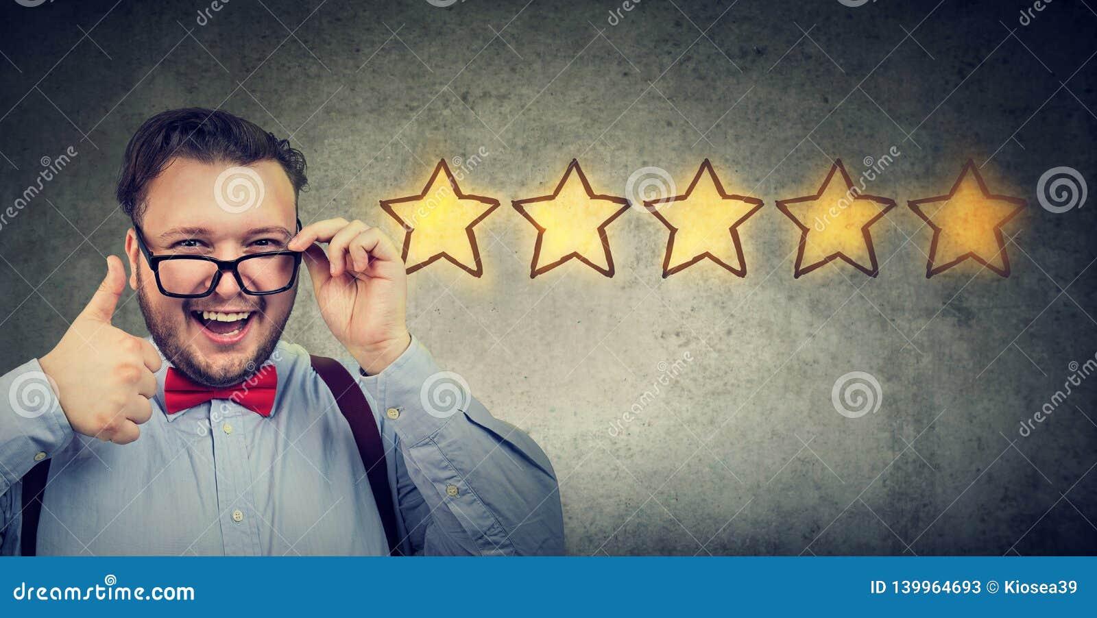 Homem considerável heerful do ¡ de Ð que sorri mostrando o polegar acima como o gesto que escolhe uma avaliação de cinco estrelas