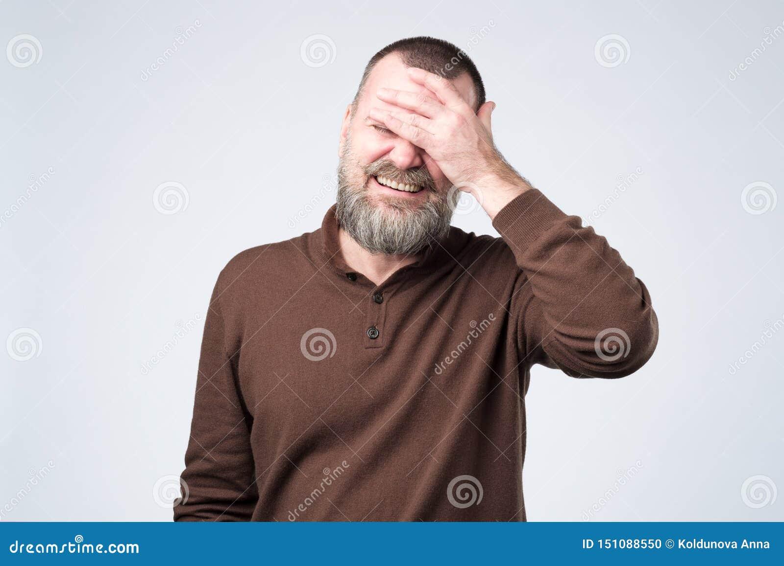 Homem considerável maduro que veste a roupa marrom que sorri e que ri com mão na cara que cobre os olhos