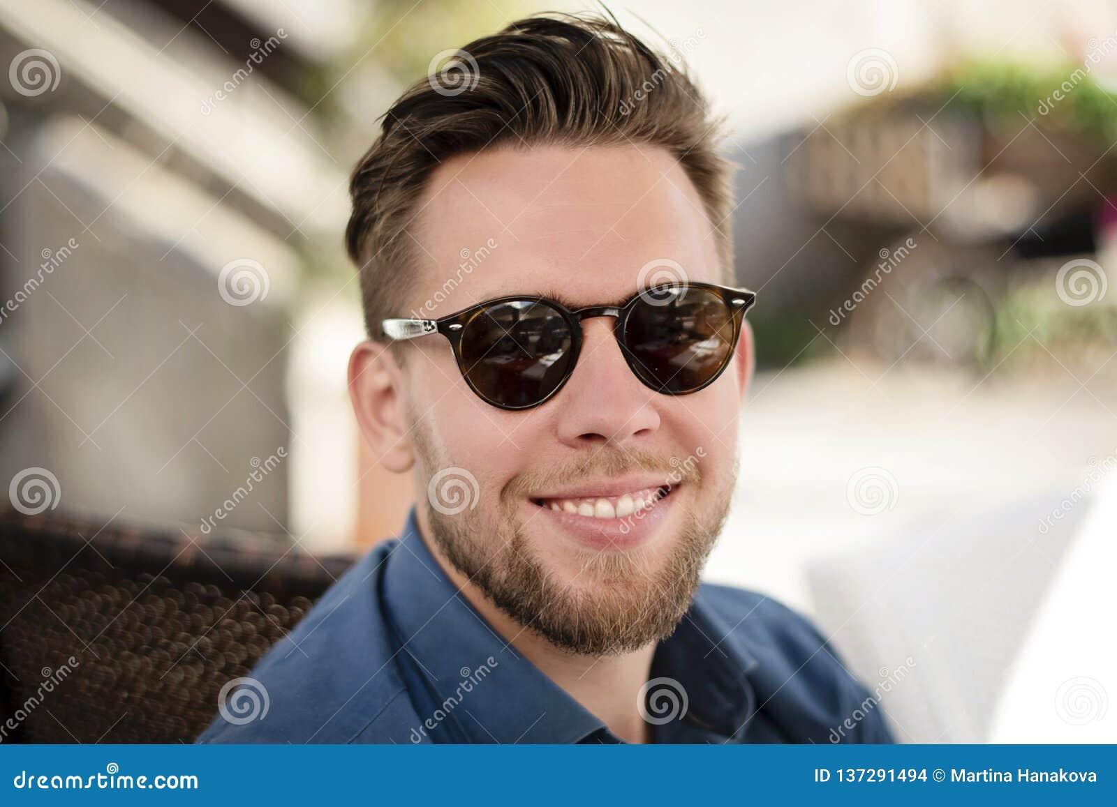 Homem considerável novo com óculos de sol que sorri fora