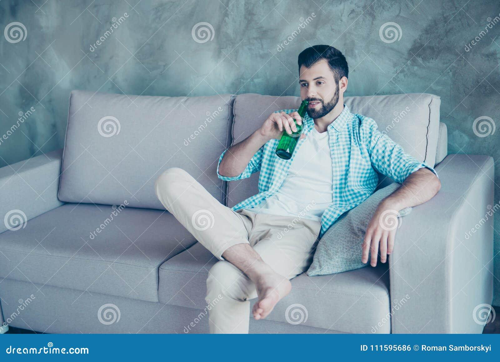 Homem considerável novo com a cerveja bebendo da cerda, pondo um pé o