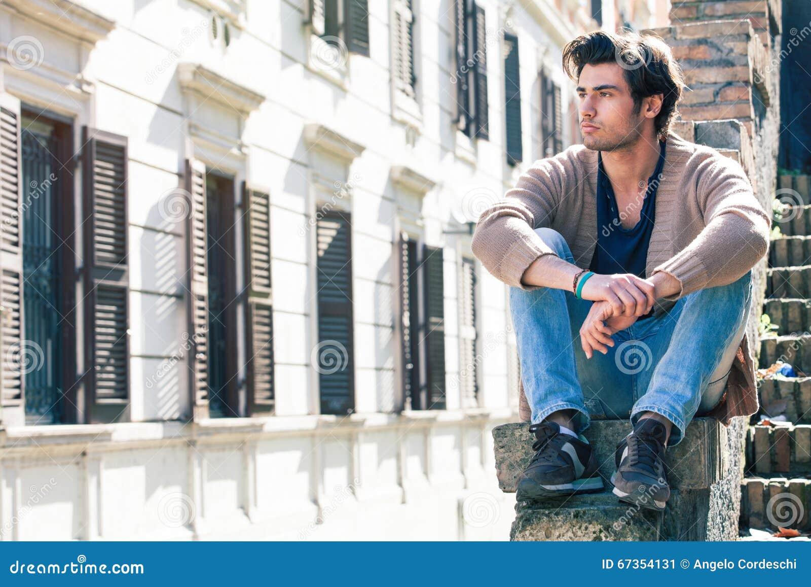 Homem considerável novo da cidade Modelo de assento urbano Edifício Windows