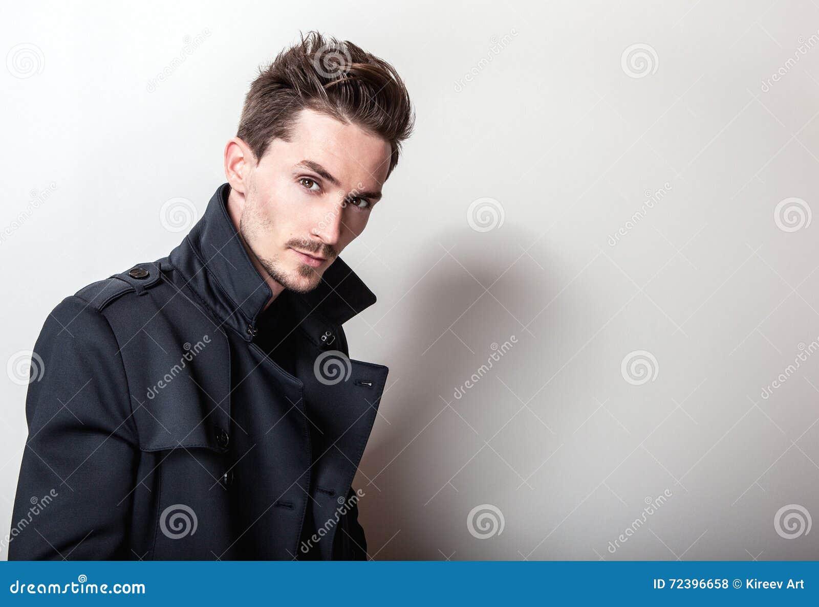 Homem considerável novo elegante na obscuridade à moda longa - revestimento azul Retrato da forma do estúdio